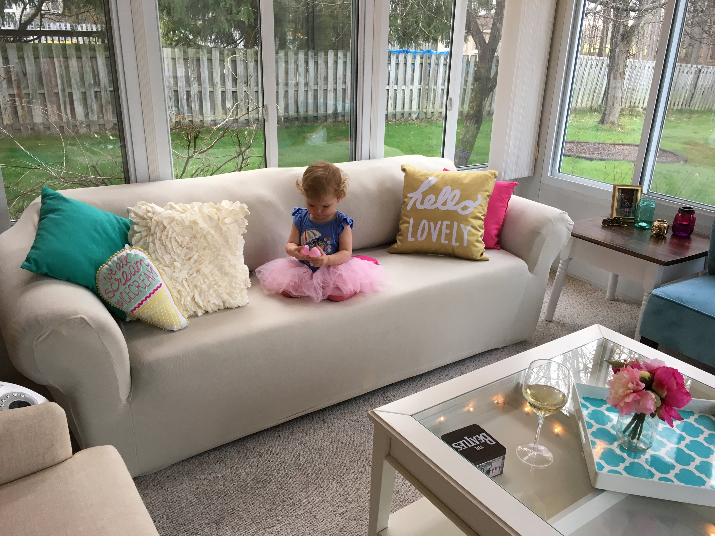 Underneath that off white slipcover is a gray-green perfectly comfortable sofa.