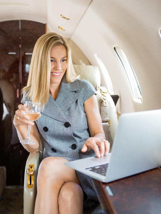 businesswoman-using-laptop-private-jet-happy-holding-wineglass-36751997.jpg