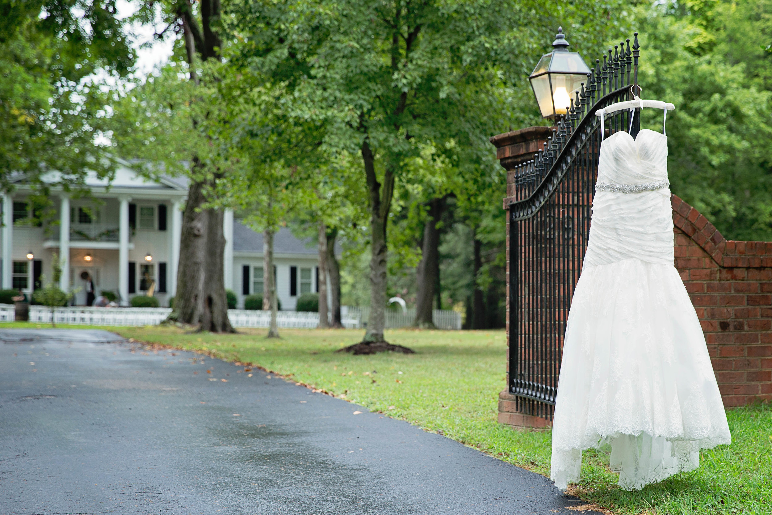 white bridal gown with crystal embellishments hanging on iron gate at virginia cliffe inn in richmond virginia photo.jpeg
