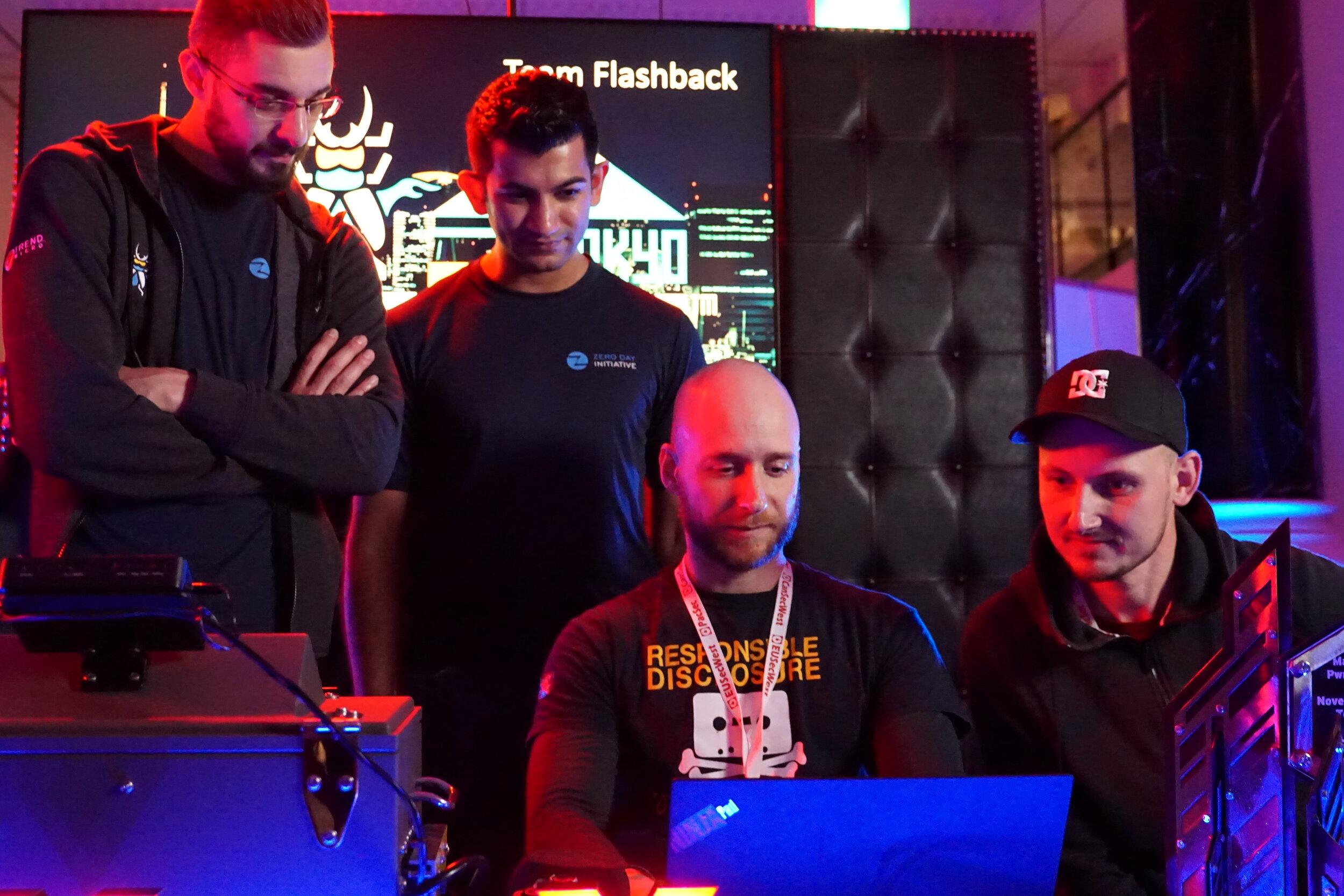 ZDI's Abdul-Aziz Hariri and Jasiel Spelman observe Pedro Ribeiro and Radek Domanski of Team Flashback