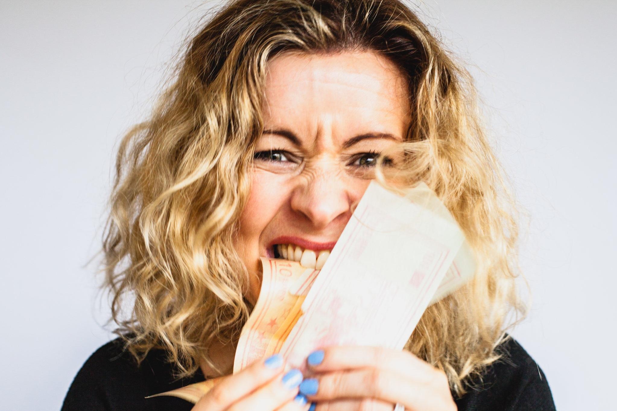 woman holding a few bills
