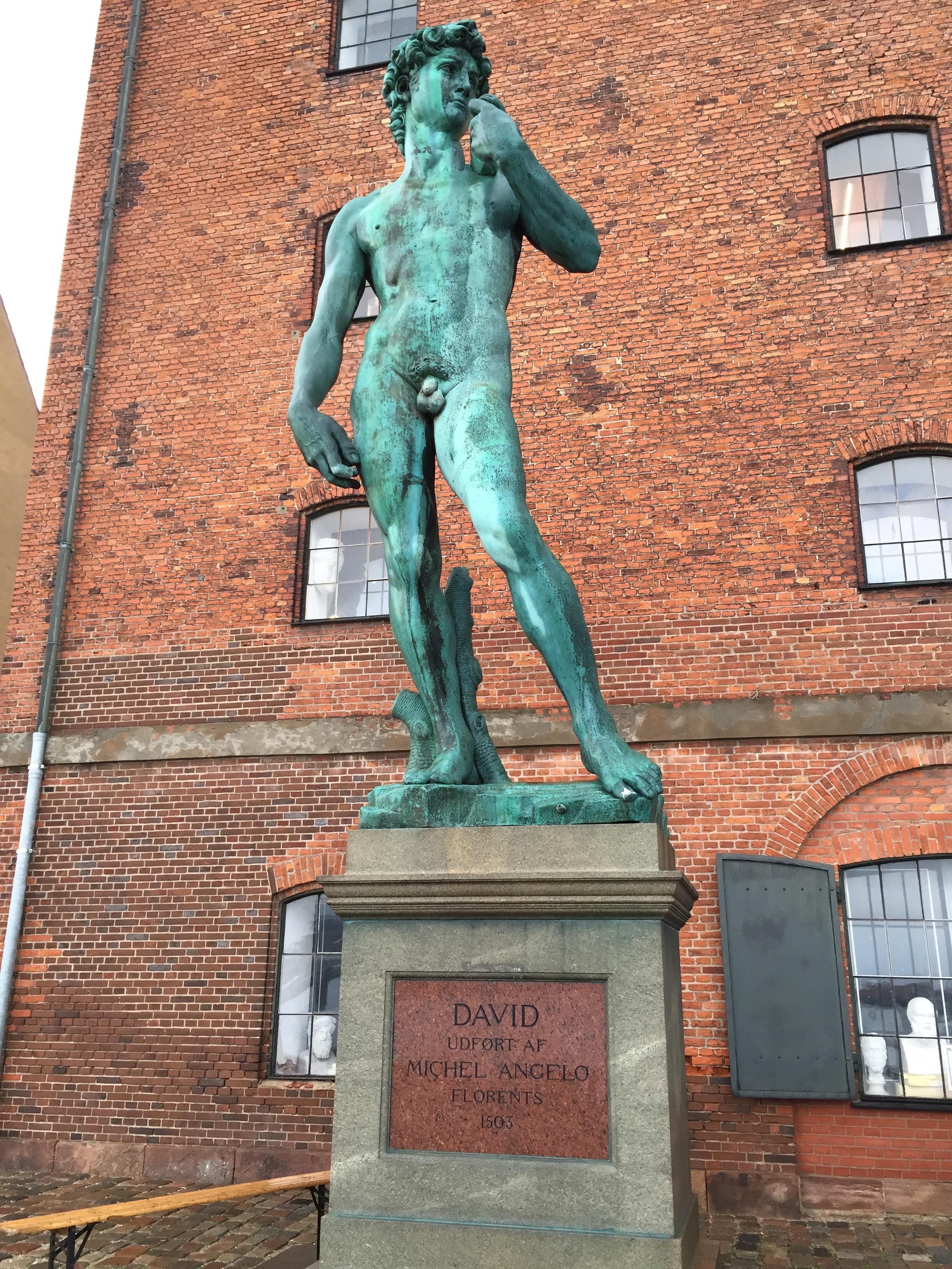 Replica of Michelangelo's  David. A bronze cast stands in front of the Kongelige Afstøbningssamling, the Danish Royal Cast Collection at the  Langelinie Promenade in Copenhagen.