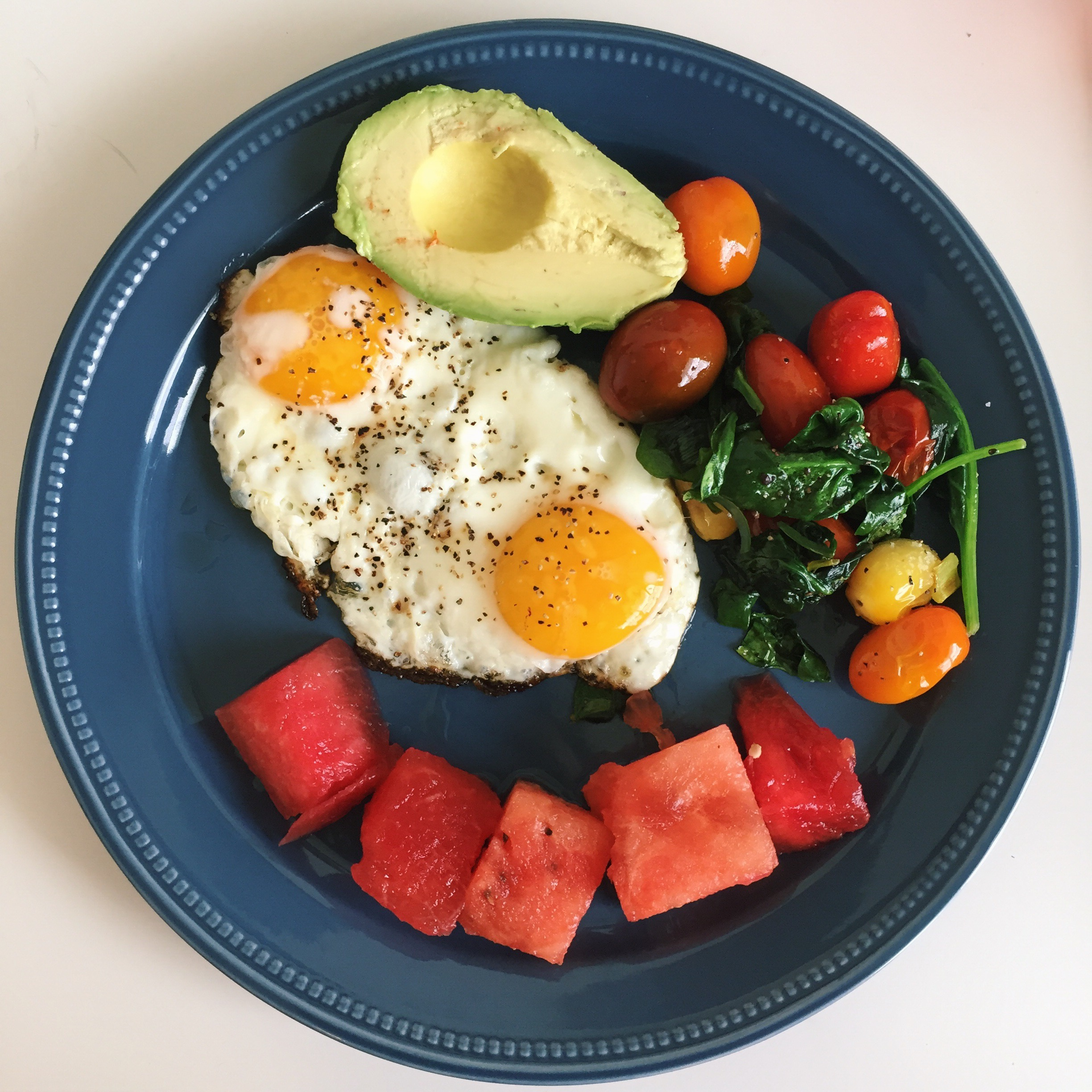 Eggs, because eggs - The most basic of all meals.-2 eggs fried in ghee in the cast iron skillet-1/2 an avocado-cherry tomatoes, spinach, and green onions sautéed in ghee-watermelonThis took me less than 10 minutes to throw together!