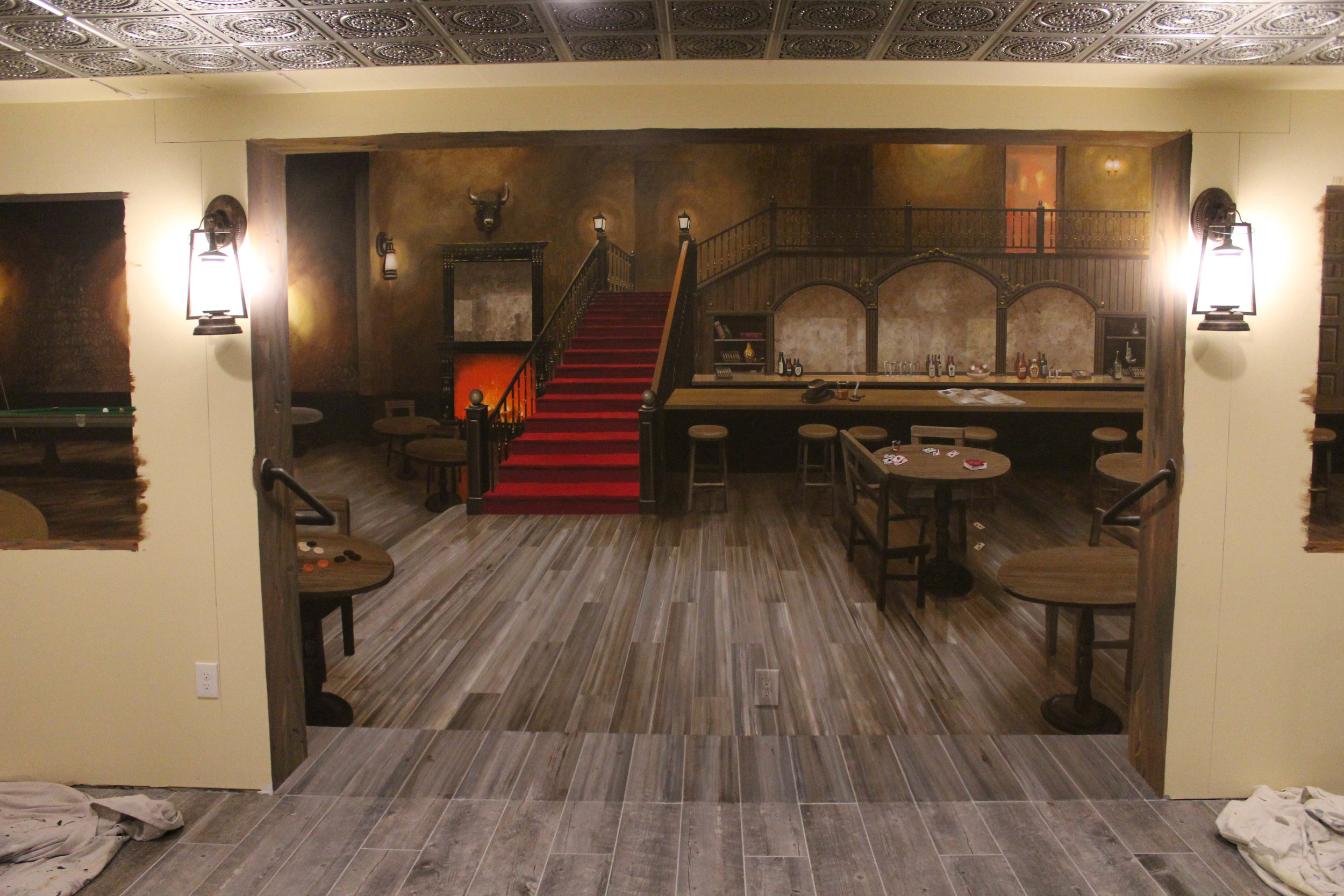 This photo shows the trompe l'oeil mural prior to the installation of surrounding trim. The floor of the room is matched into the mural to create the sense that the room continues. The scene within the mural depicts an old western hotel lobby and bar. The details within the mural will be echoed in reality by the details within the actual bar room.