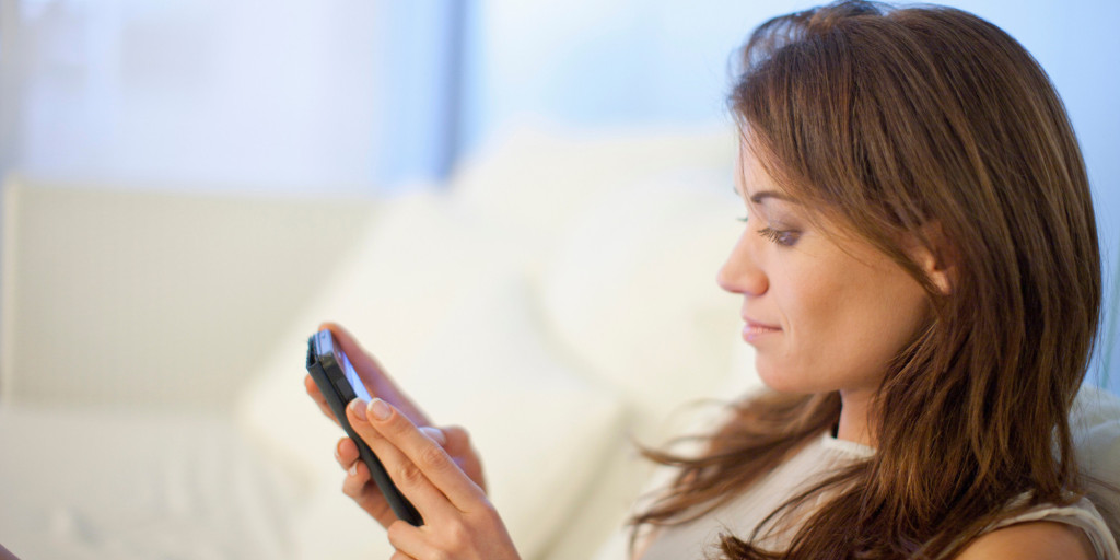 Woman using mobile phone in hotel lobby