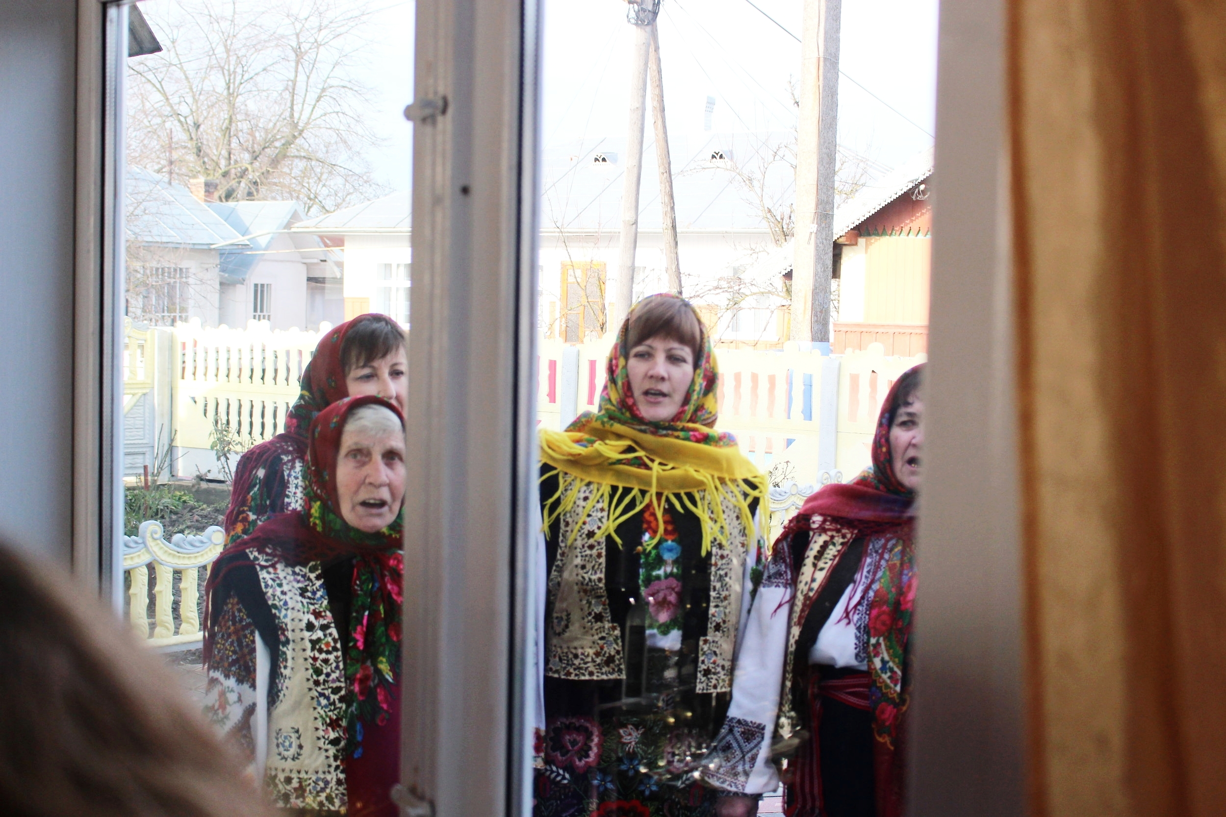 The carollers started singing by the window before the hosts invited them in.