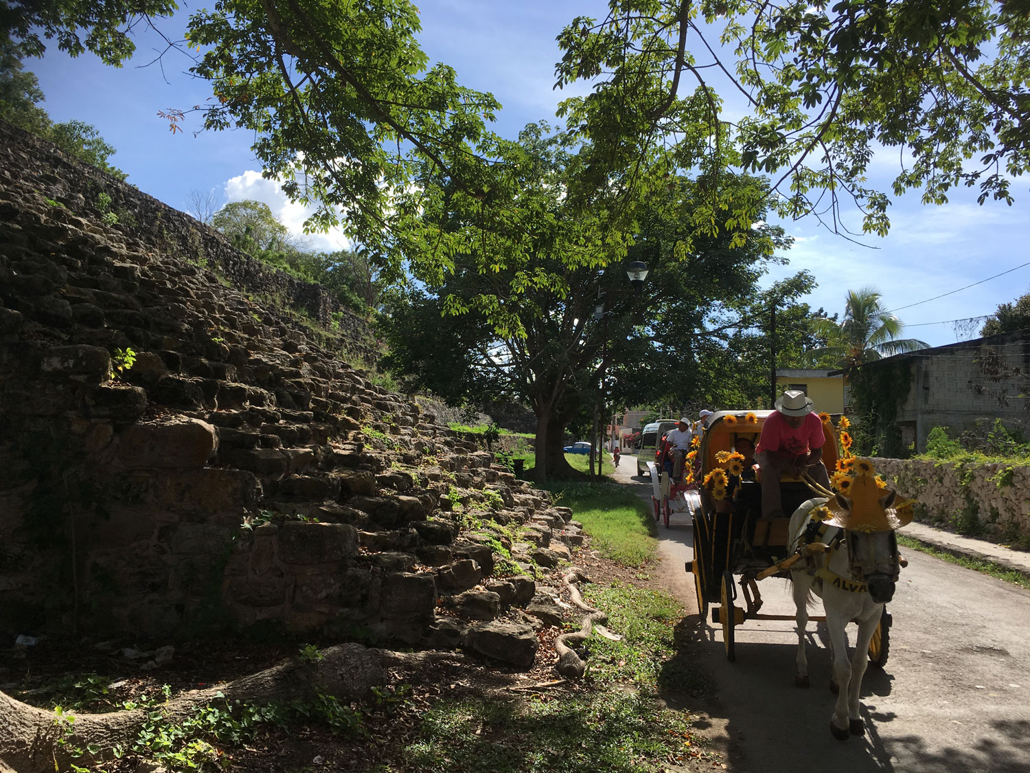 A horse carriage passing the base of the K'inich pyramid.