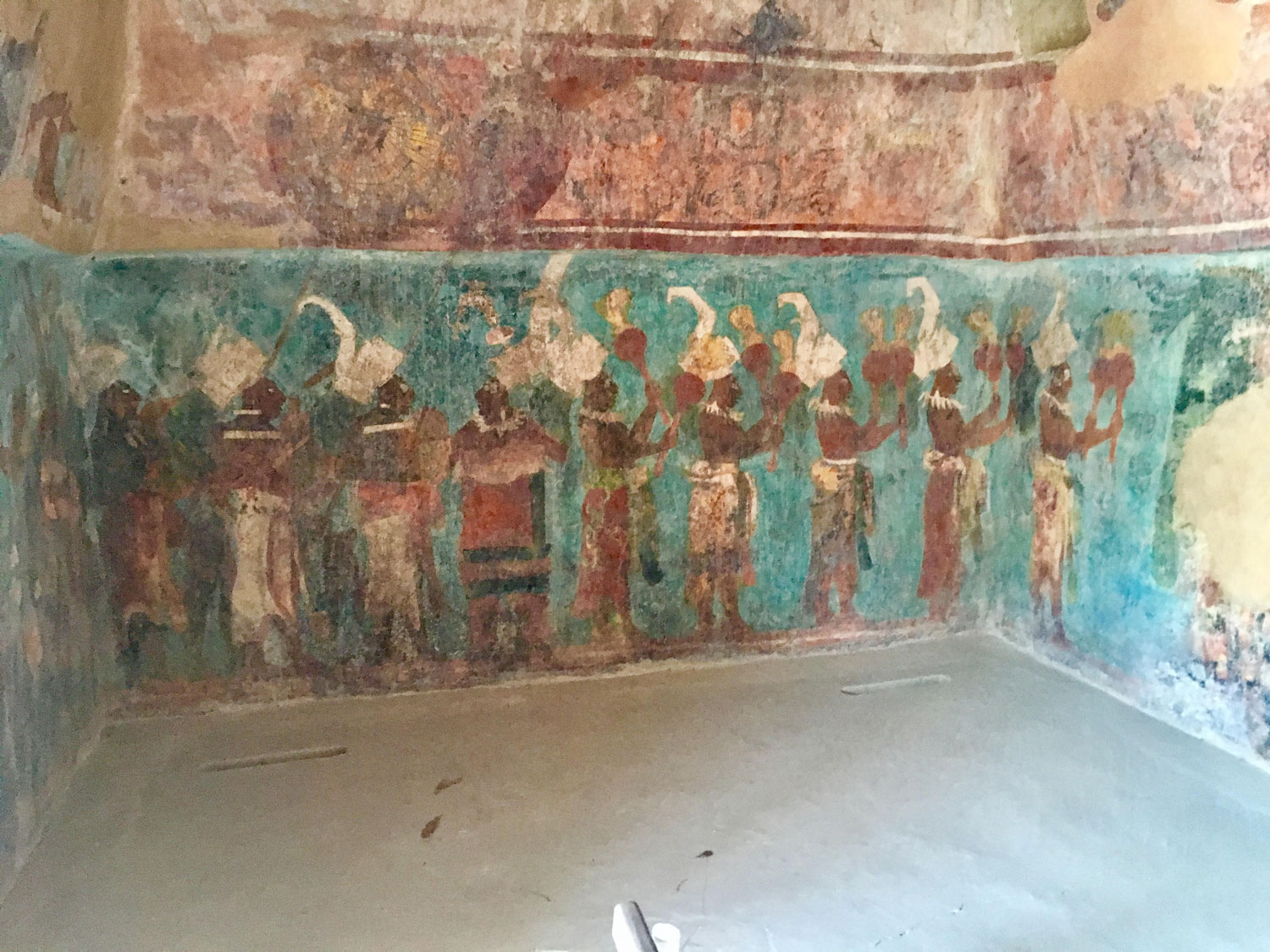 Musicians from Bonampak murals, wearing skirts and headdresses, playing gourd rattles, wooden drums, and trumpets.