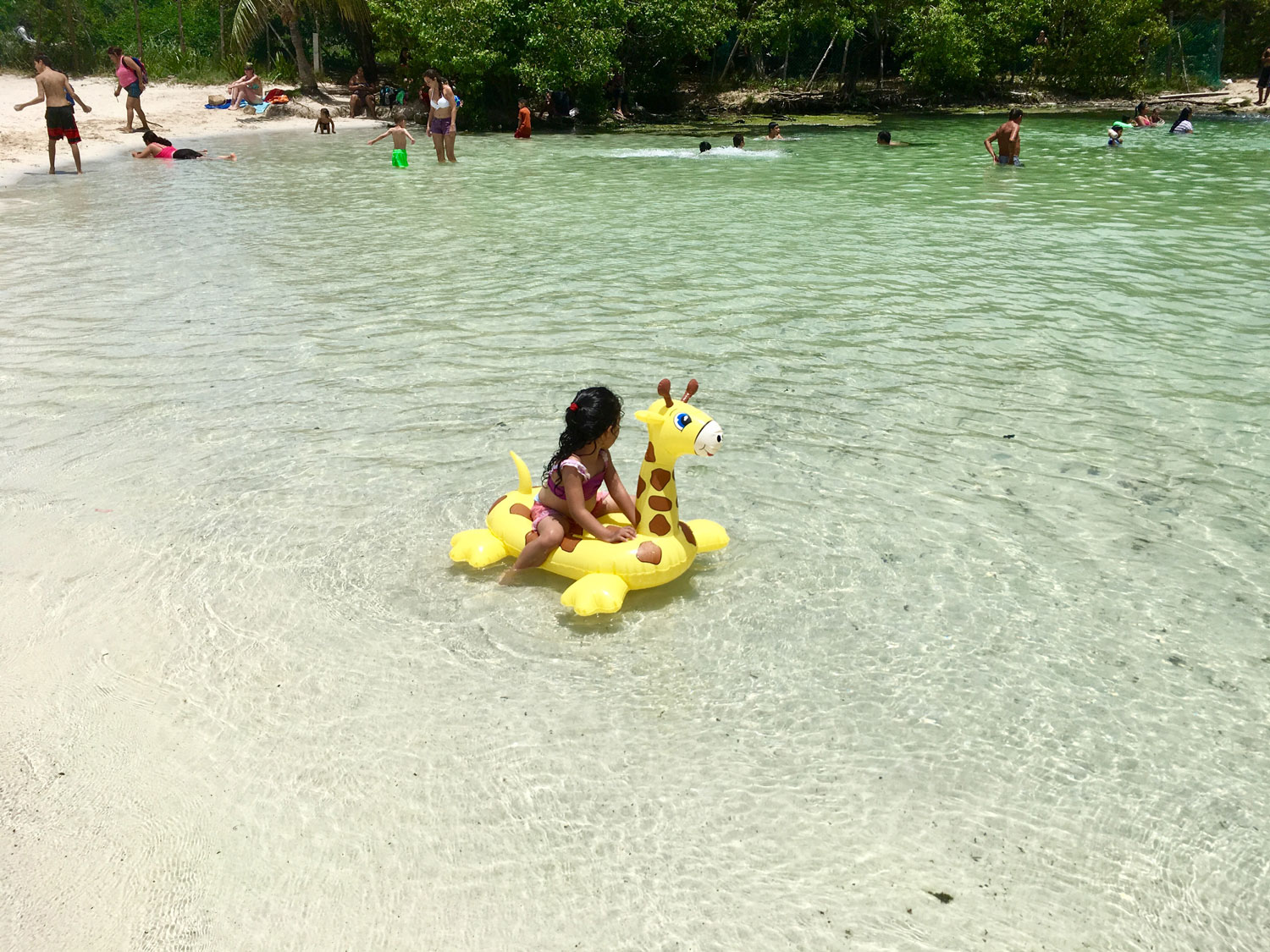 Children love playing in the shallow cenote while teenagers (on the right) prefer jumping in the deeper cenote.