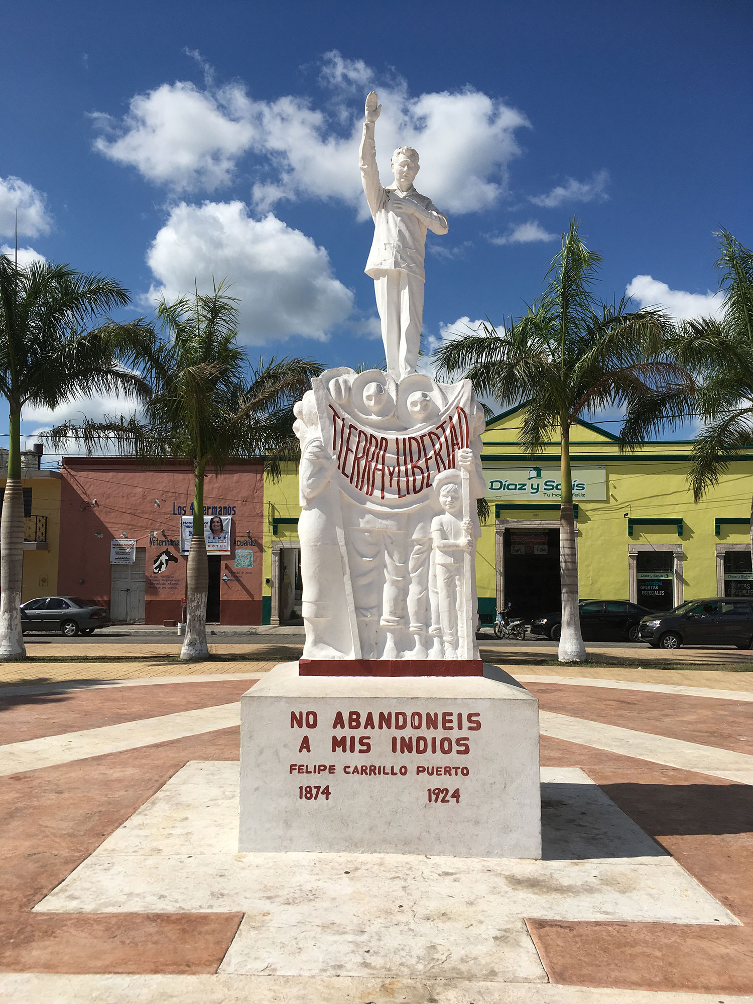 A statue of Felipe Carrillo Puerto at the park flanked by the church.