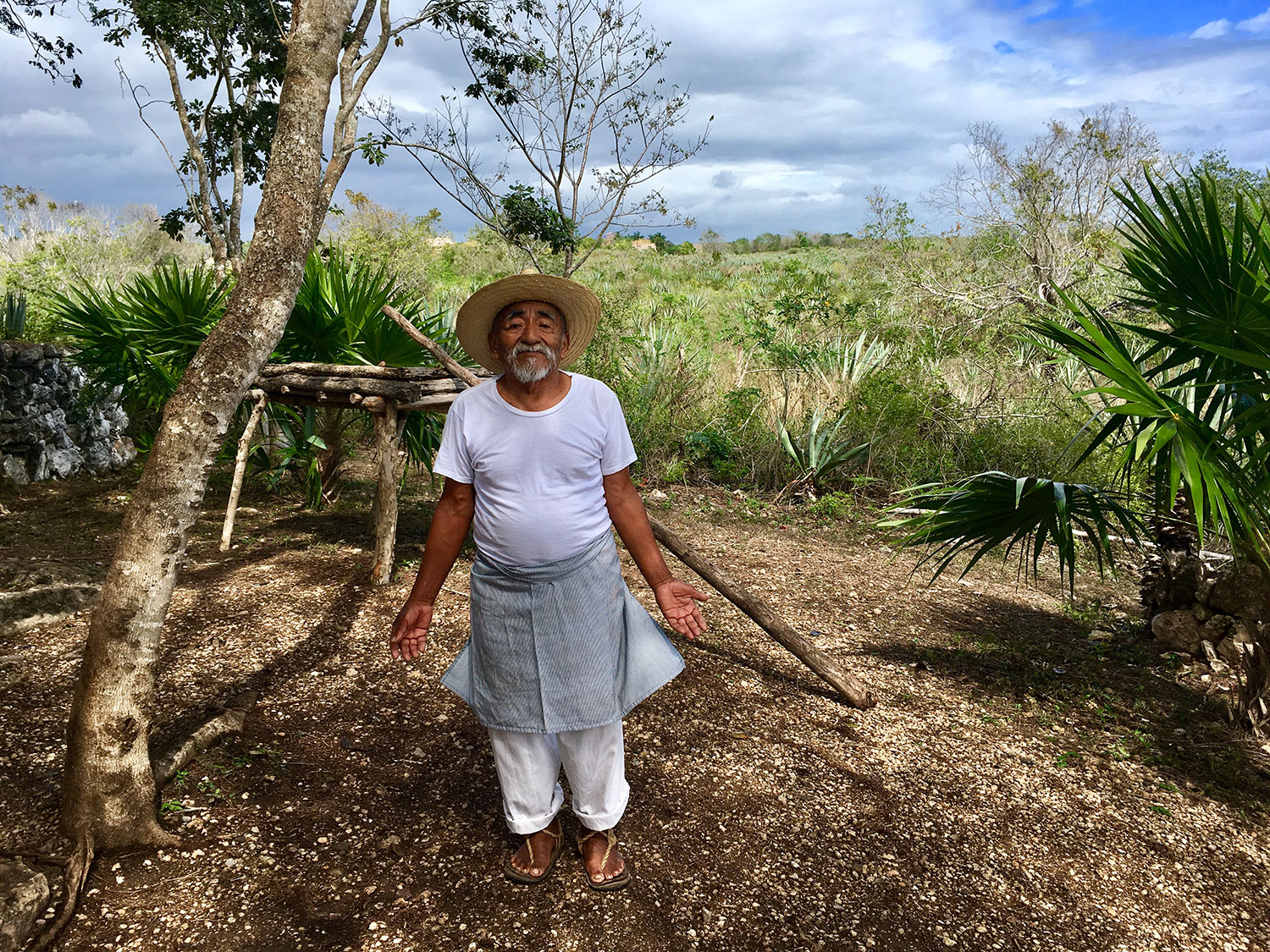 Don Antonio used to work on the hacienda as a child. Today he shows the visitors a Maya hut in the fields (on the right).
