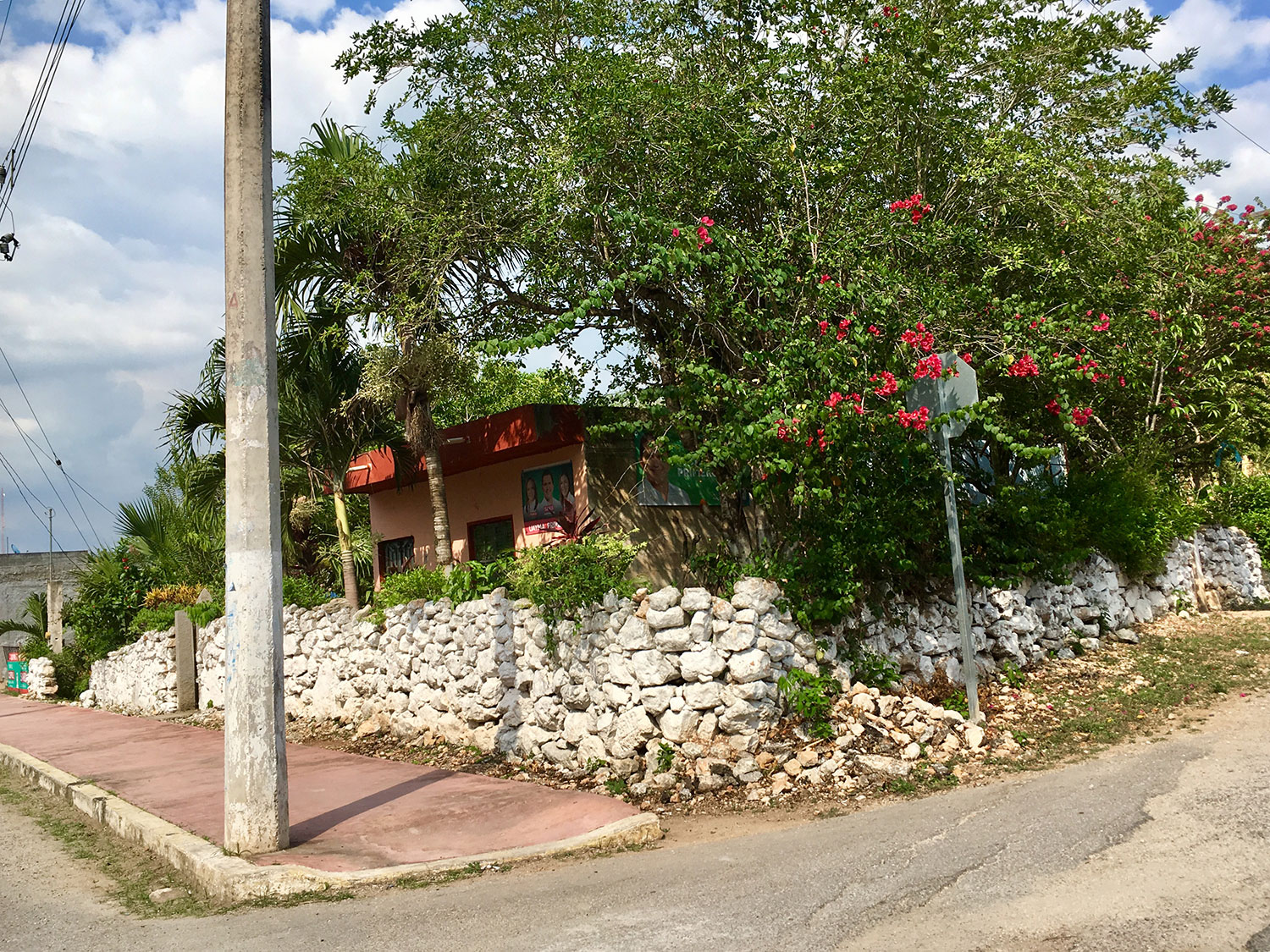 Typical village houses of Yucatán, with a stone wall.