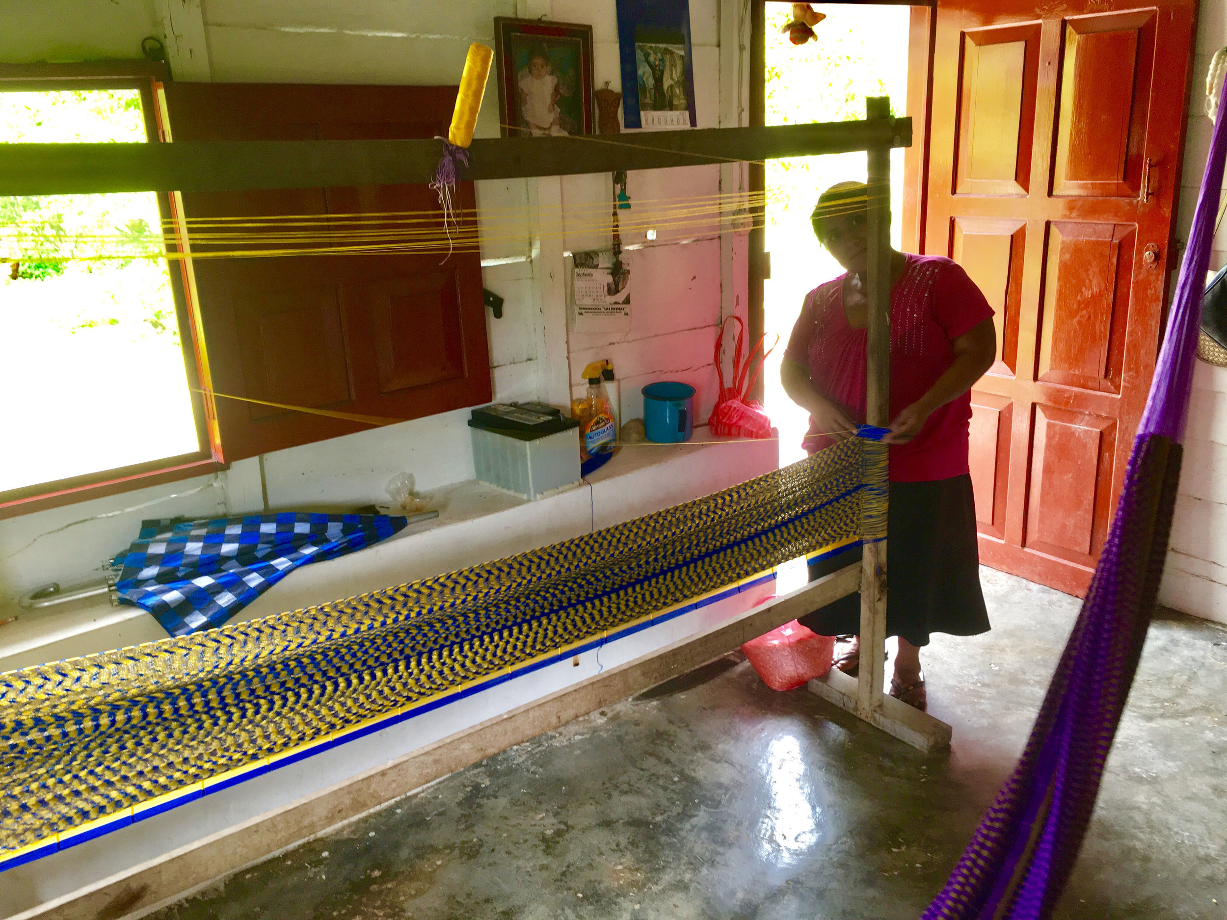 Fabiana weaving a hammock.