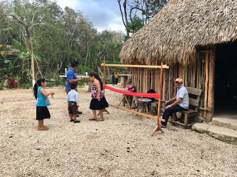 Children run around while adults weave hammocks (for sale).