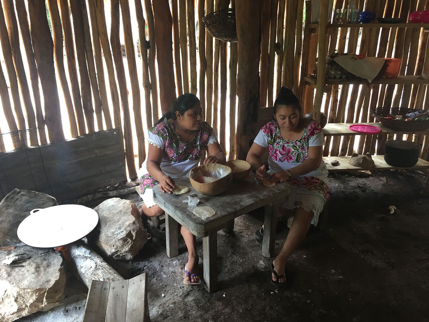 The same kitchen but during different visits. The women wear  huipils .