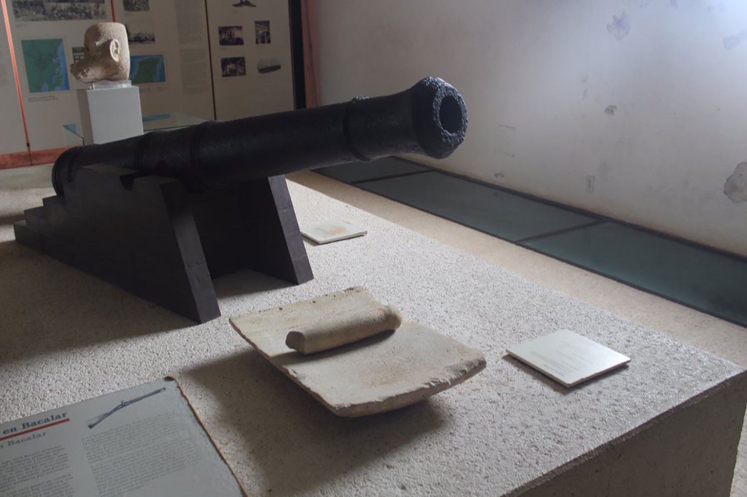 Two objects, two symbols of different cultures: metate (a Maya stone for grinding corn) and a Spanish cannon.