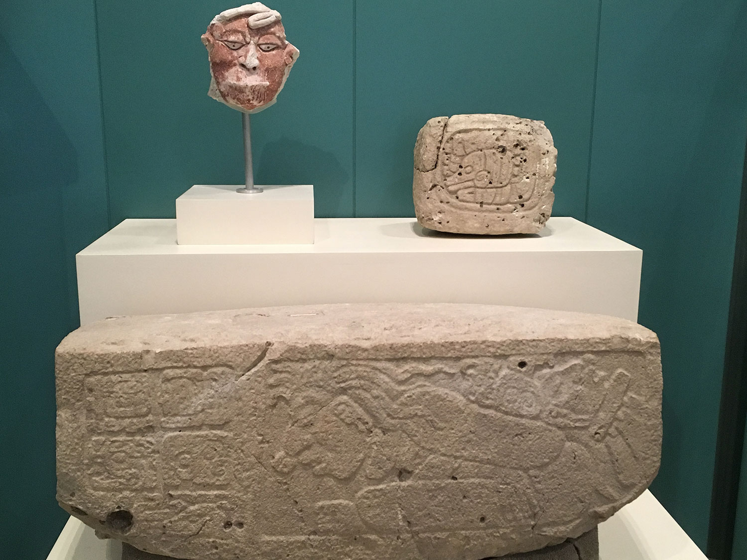 The mask of a captive, the glyph and the step with the captive frieze, displayed at the Cancún Mayan Museum.