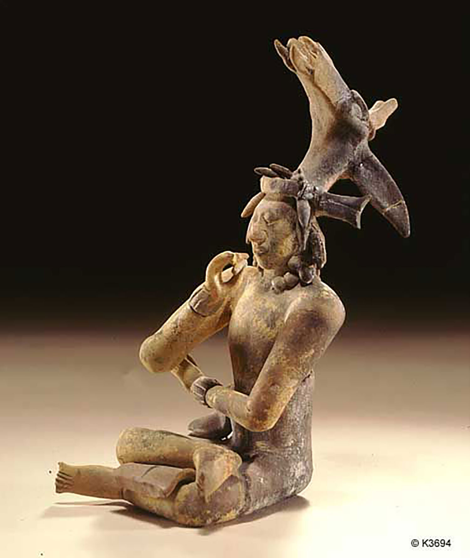 Seated noble with deer headdress, smoking cigar, sculpture from Jaina island. Photo by Justin Kerr. Source:  pinterest.com.mx .