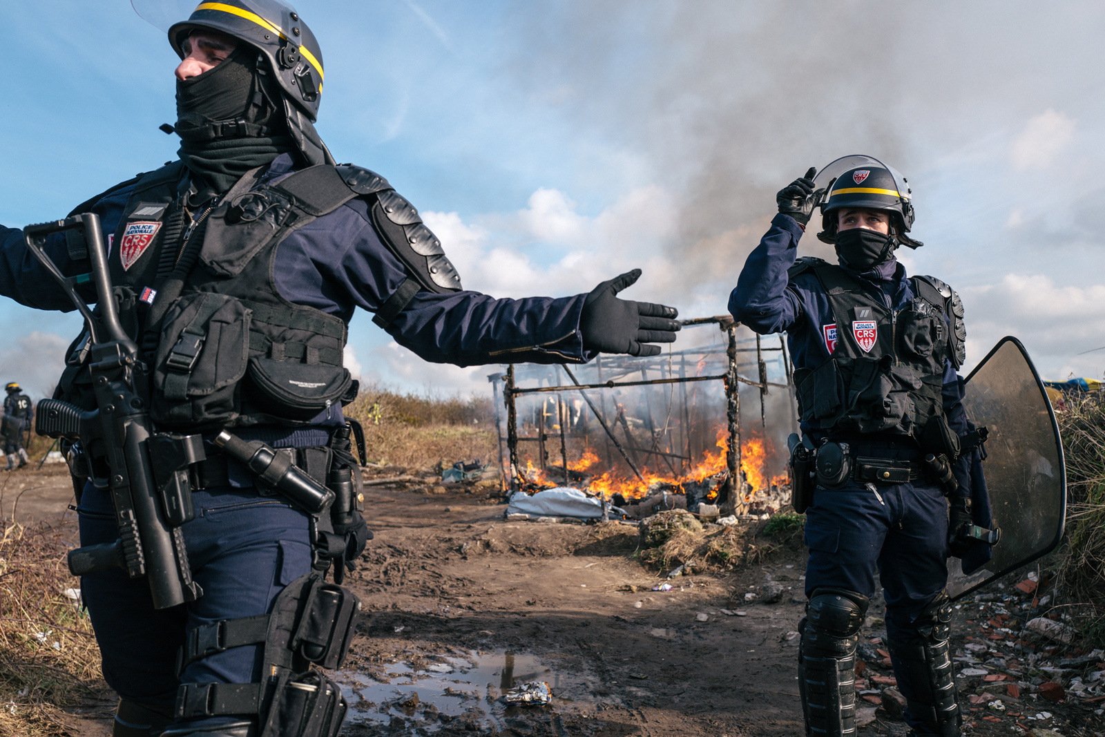 Police officers direct people away from a burning shelter in March 2016.   Photograph: Rob Pinney for Point.51