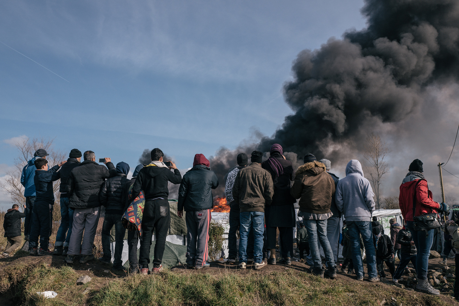 "People watch as a shelter burns during the eviction of the southern part of the ""Jungle"" camp in March 2016.   Photograph: Rob Pinney for Point.51"