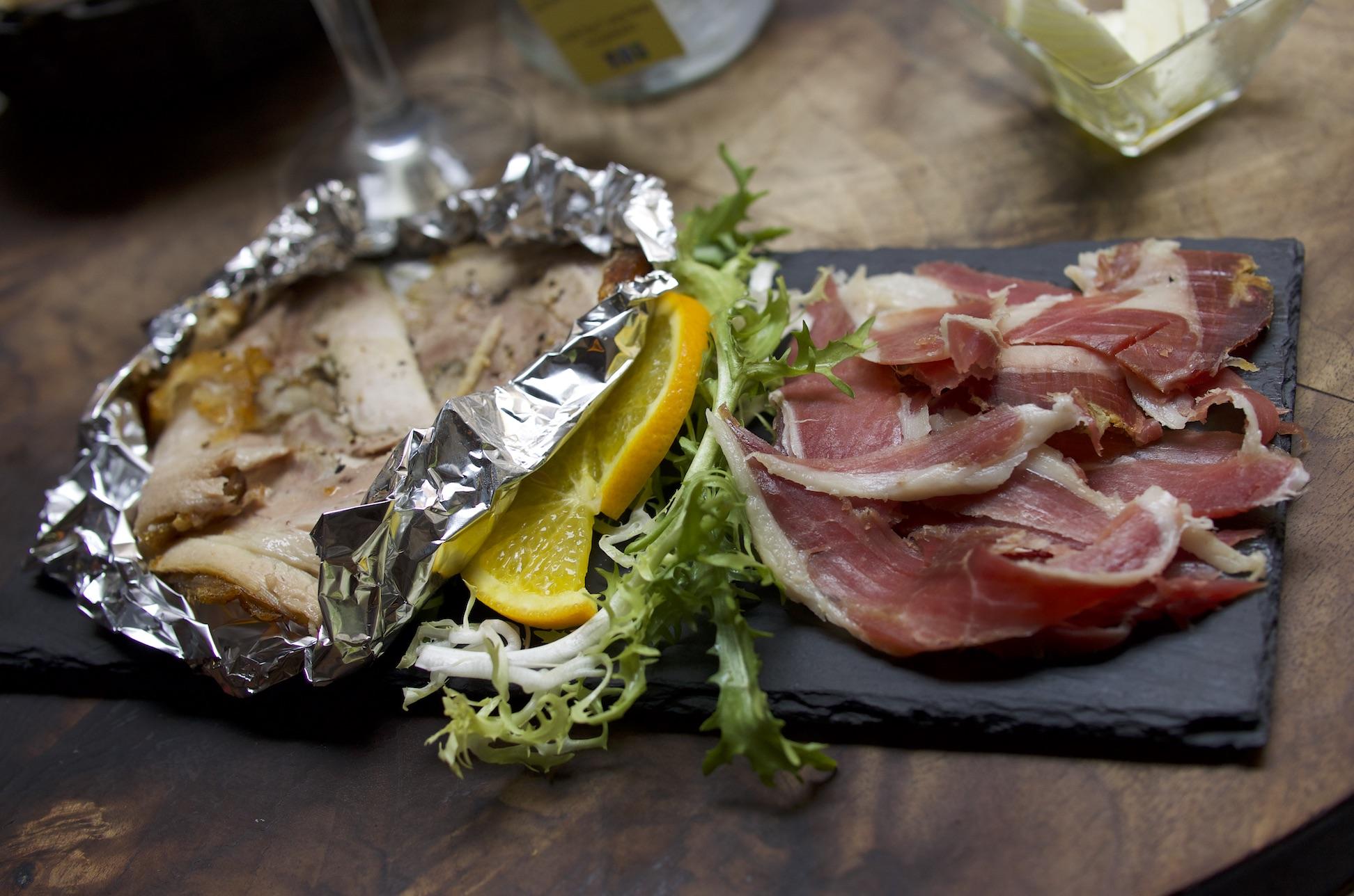左边是Porchetta,右边是生火腿。  Porchetta 是意大利的烤猪肉,是将整扇新鲜猪肋的骨头剔除、加入调料揉捏后卷成圆柱状后用绳子捆绑再进行烤制。由于是整片肉、且有肥有瘦,因此即使是切片后的 Porchetta ,肉汁也非常饱满、肉香十分浓郁、肉质酥软且肥而不腻,绝对是不可错失的意大利美味。而且 Porchetta 源于罗马地区,因此在罗马更应该尝尝。罗马的许多餐厅、小馆、甚至是超市都供应这一道美味。