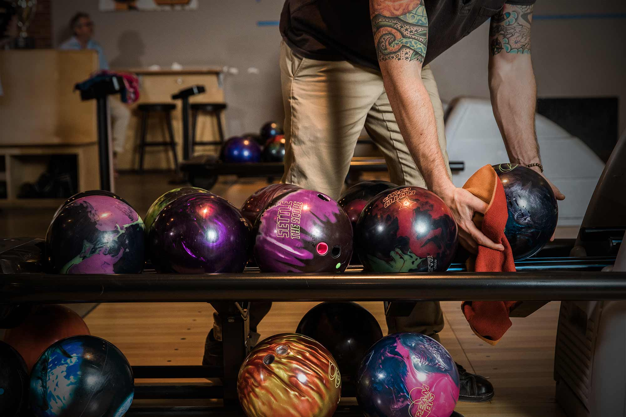 Colorful bowling balls being picked up by man with tattoos