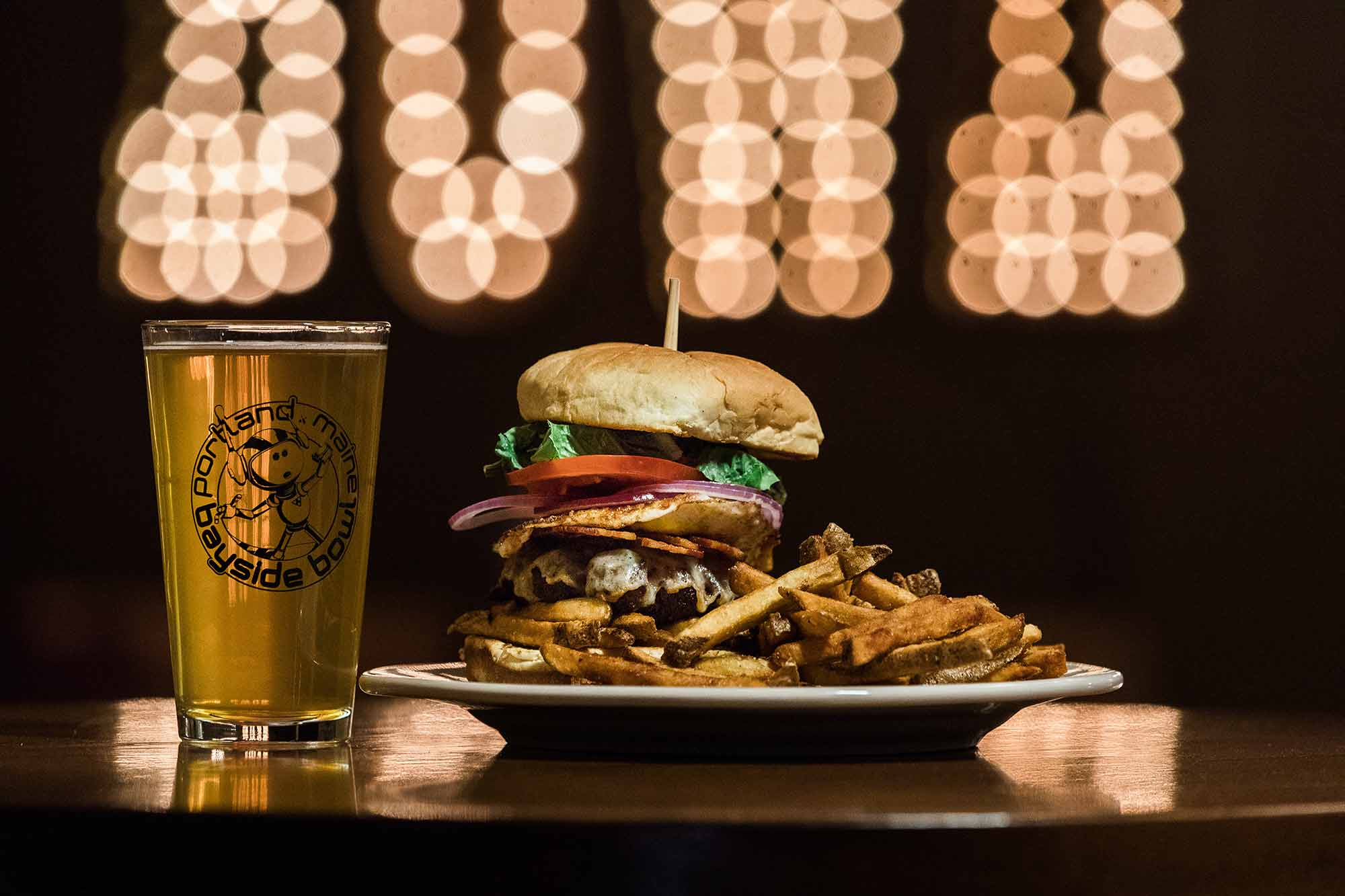 Burger and a beer with Bayside Bowl logo on glass