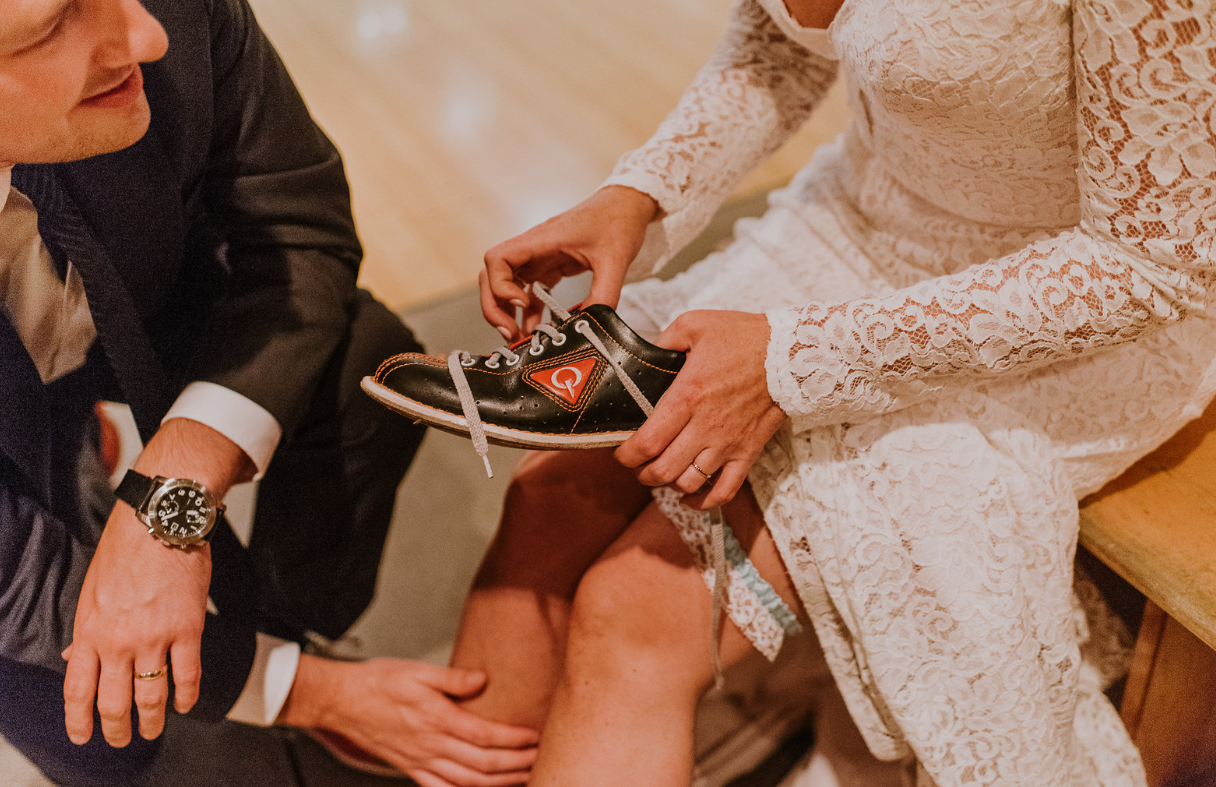 Bride laces bowling shoes with watchful groom