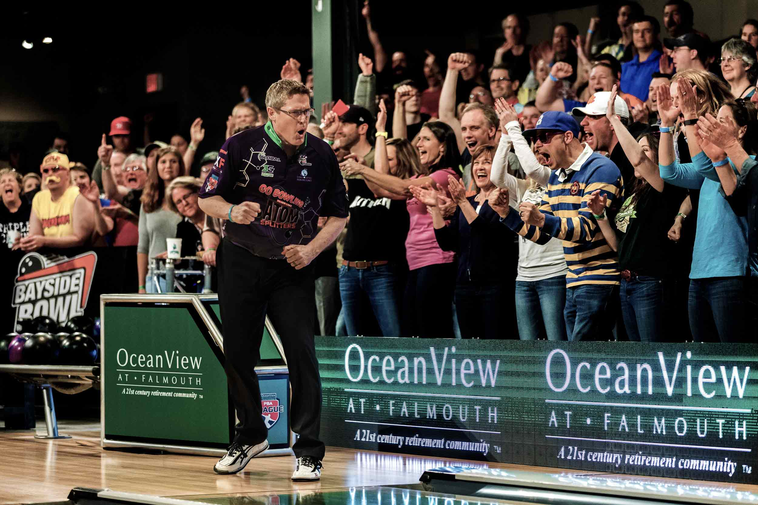 Professional bowler pumping his fist in front of large cheering crowd at Bayside Bowl