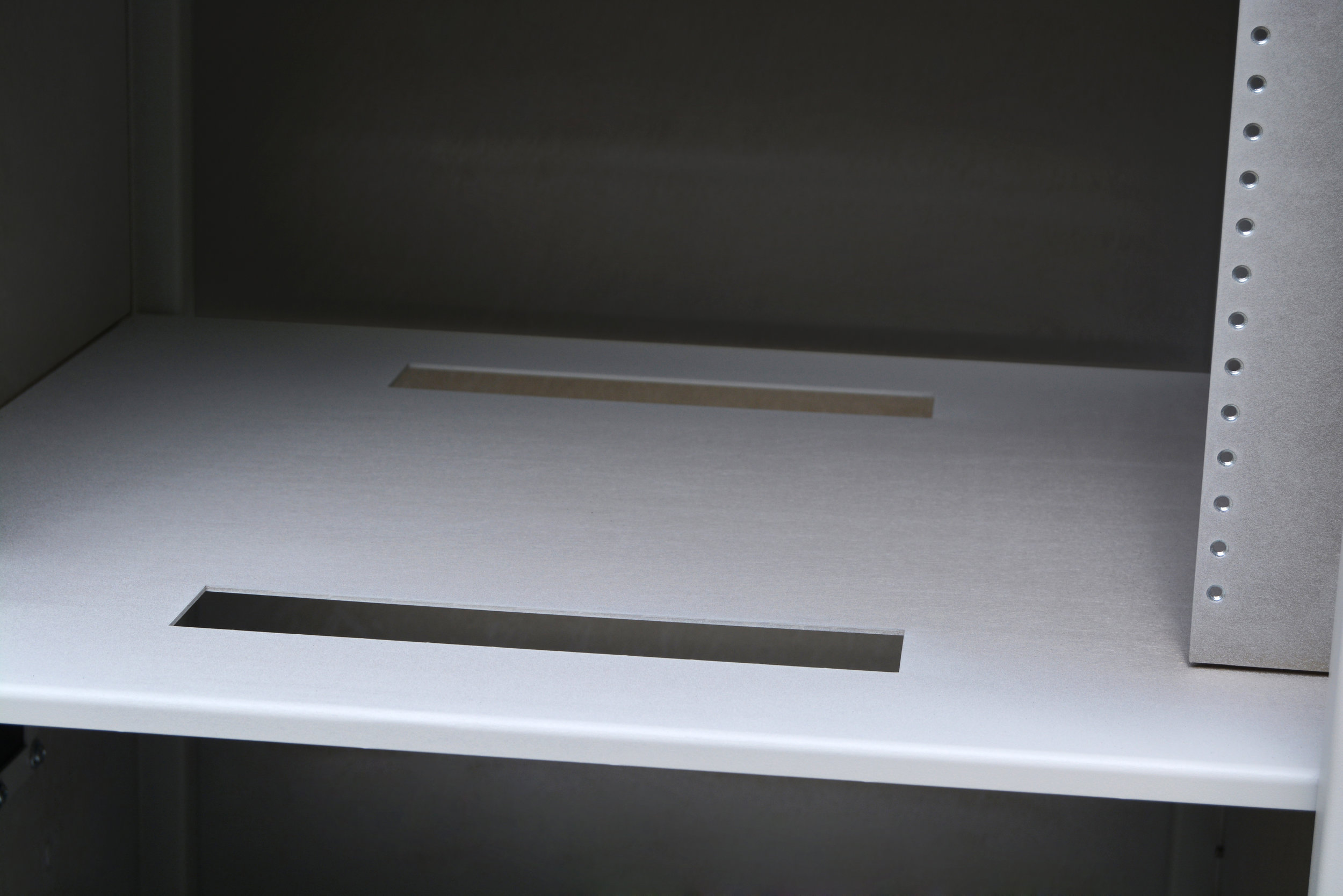A dividing shelf splits the enclosure in two allowing for the separation of necessary equipment. We cut two cable passthrough options, one in front and one in back for easy access to cable feeds.