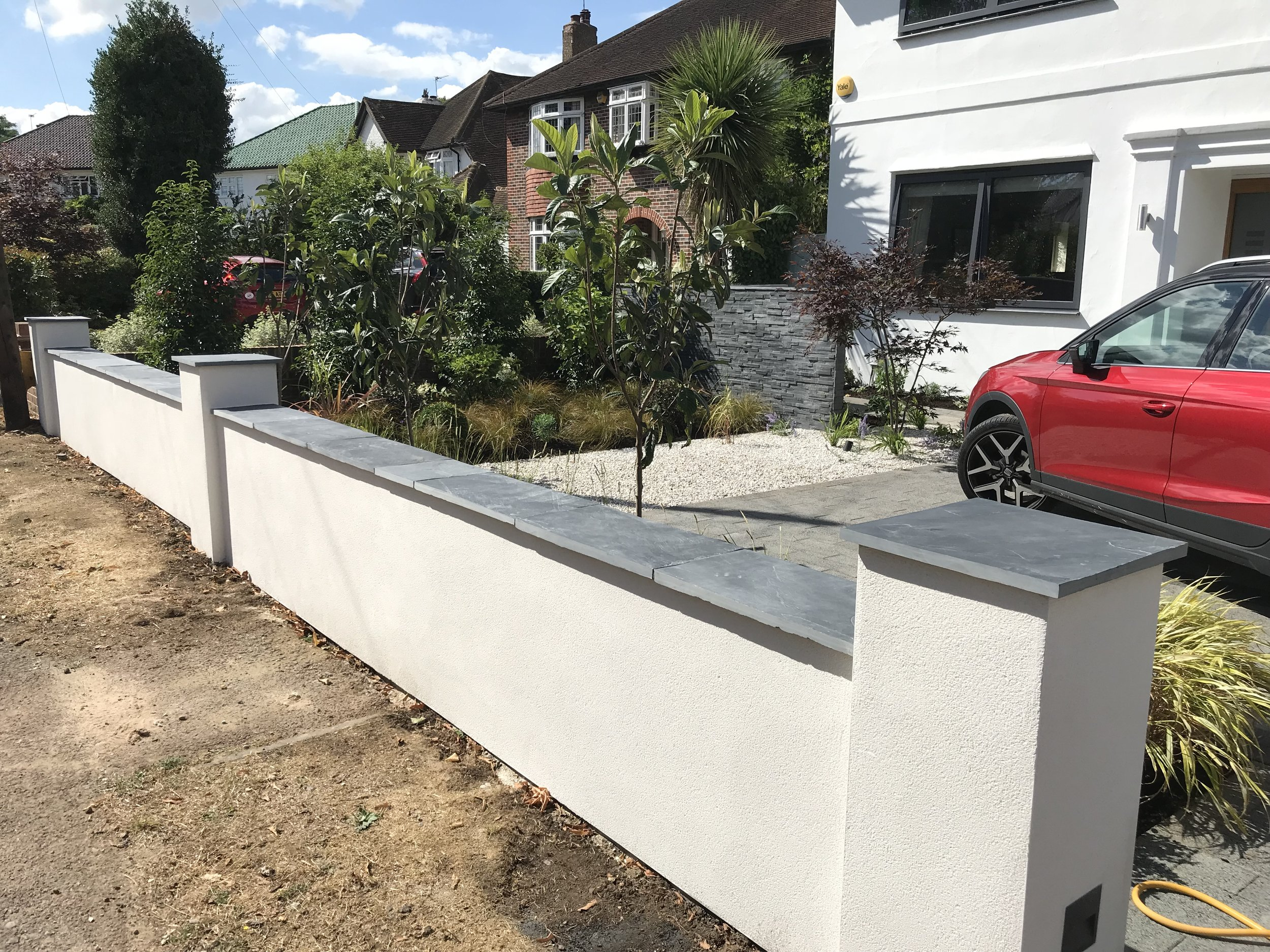 Concrete block wall rendered using white K1 K-rend, wall capped with Blue black slate, Esher 2018.
