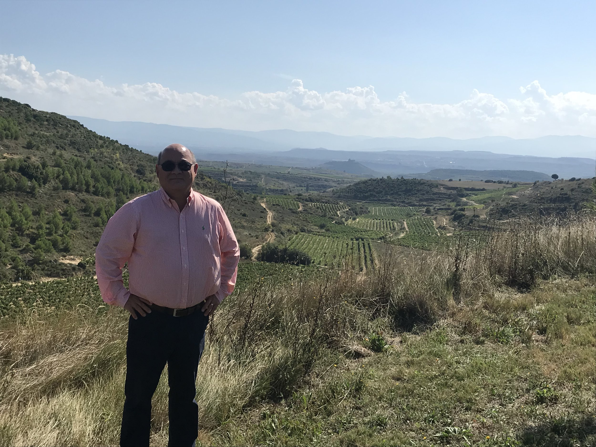 Standing on the grounds of Santa Maria de la Piscine with vineyards below and mountains in the distance.
