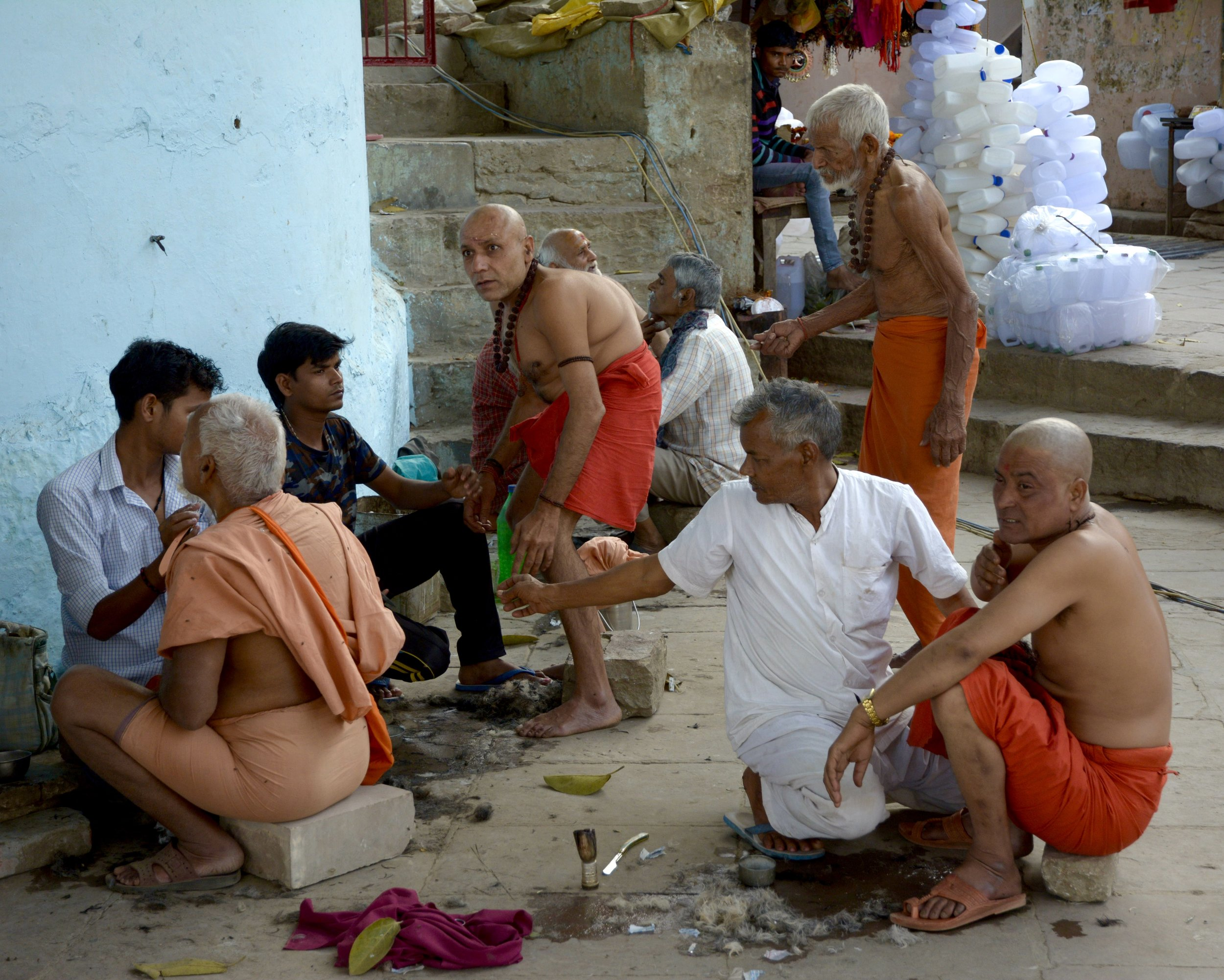 Sadhus and grieving family members having their heads shaved.
