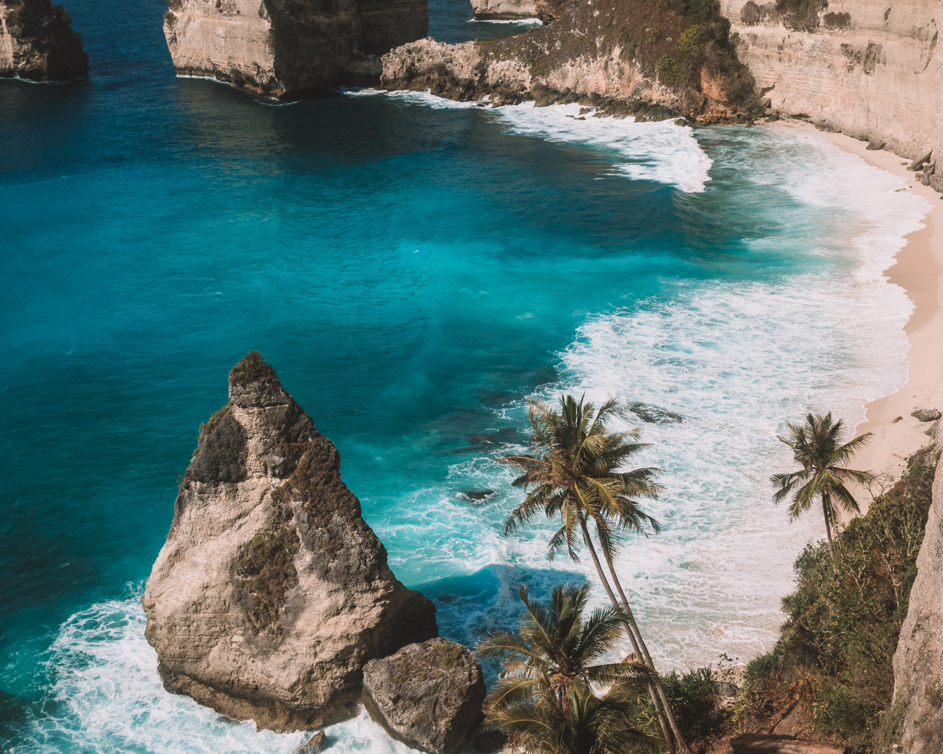 travel guide to Nusa Penida island Bali indonesia freeoversea couple tropical destination dream beach most beautiful beach palm tree and rock formation