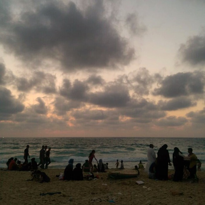 KHAN YOUNIS | Sun sets in Khan Younis as families relax together by the beach. From the far left, the twinkle of Israeli naval boats dot the horizon. July 11, 2016.