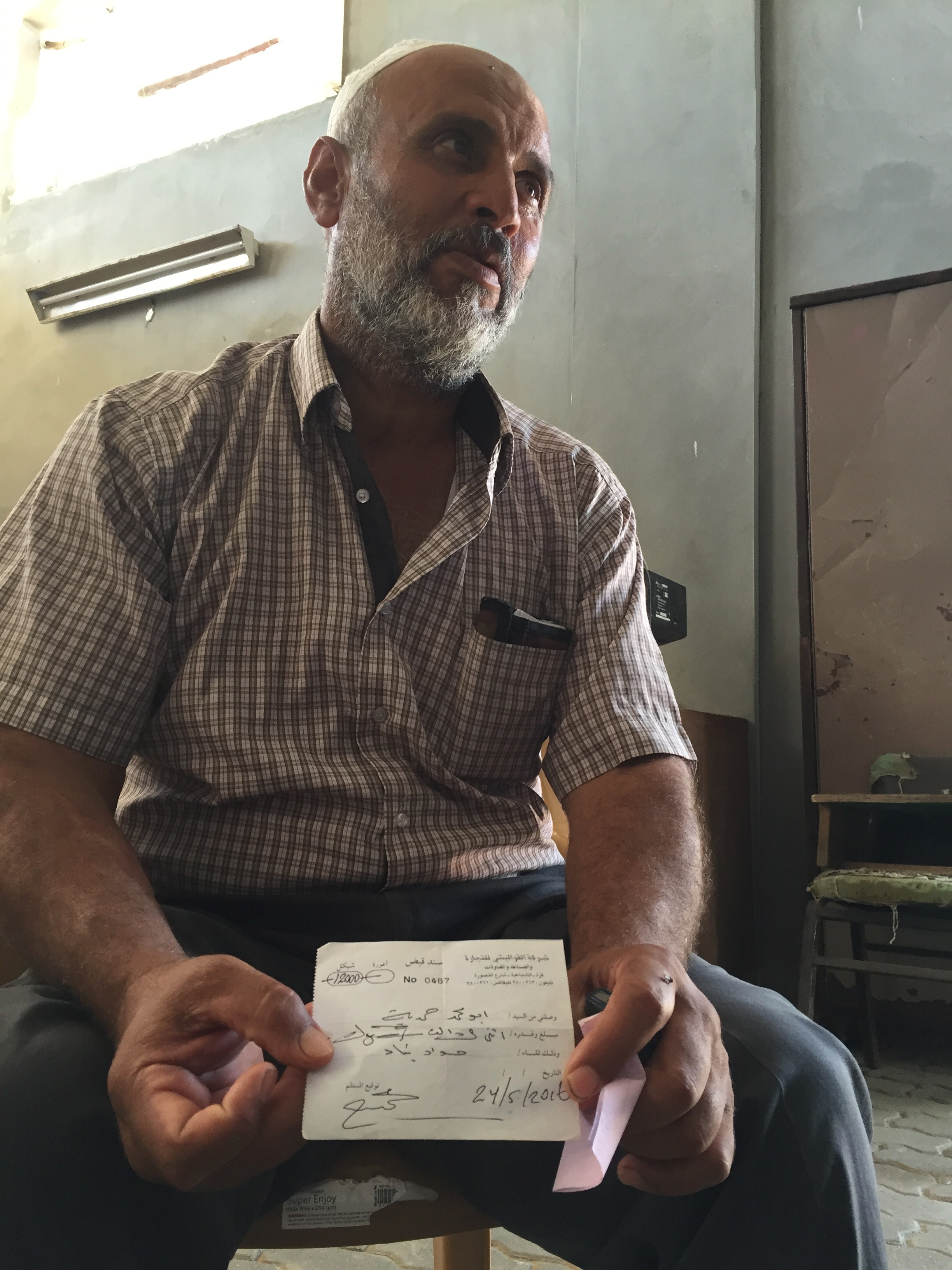 SHUJAYA | Moussa's entire four-storey home was destroyed during the 2014 Gaza war. He shows us a receipt proving he paid the money acquired from a Kuwaiti reconstruction fund to a cement provider in Gaza, but he says he is still waiting for the delivery to rebuild his home. July 10, 2016.