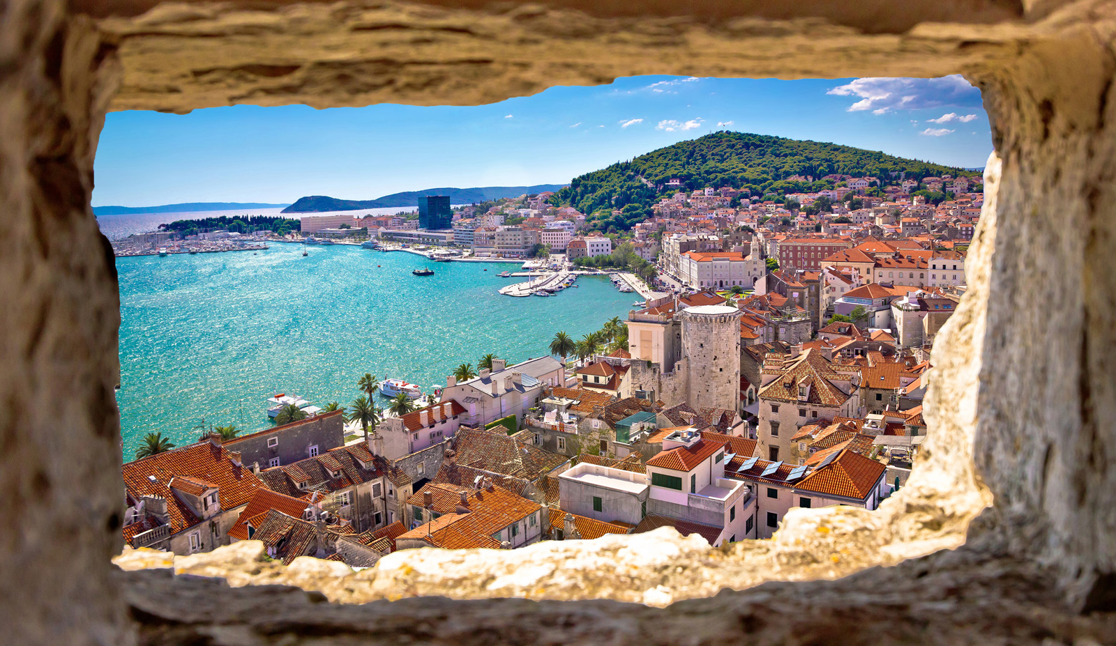 Looking through an old stone window to beautiful port