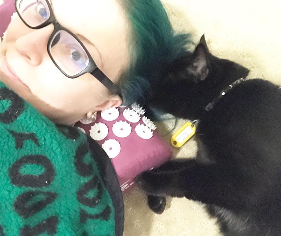 Me using the acupressure mat and pillow while guest cat Martok nests in my hair. He LOVES my hair.