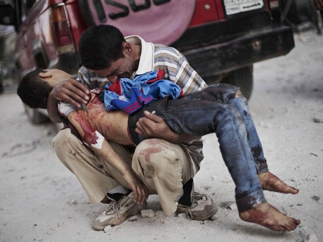 Adult man holding a young boy's corpse on his arms, during the war in Syria.  Children are extremely vulnerable to airstrikes, bombing and shelling.