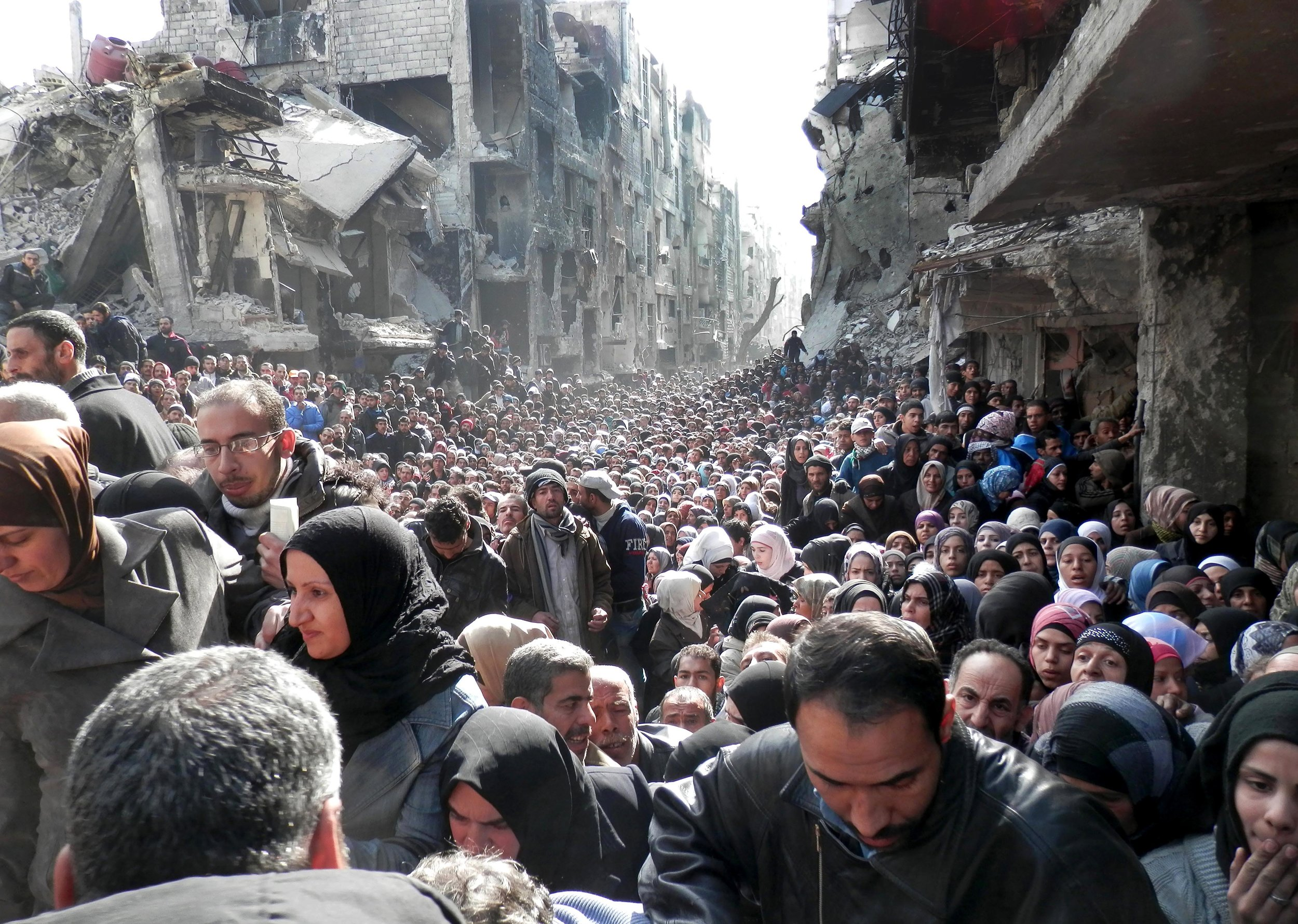 Residents of the besieged in Yarmouk line up to receive food supplies in Damascus, Syria, Jan. 31, 2014.