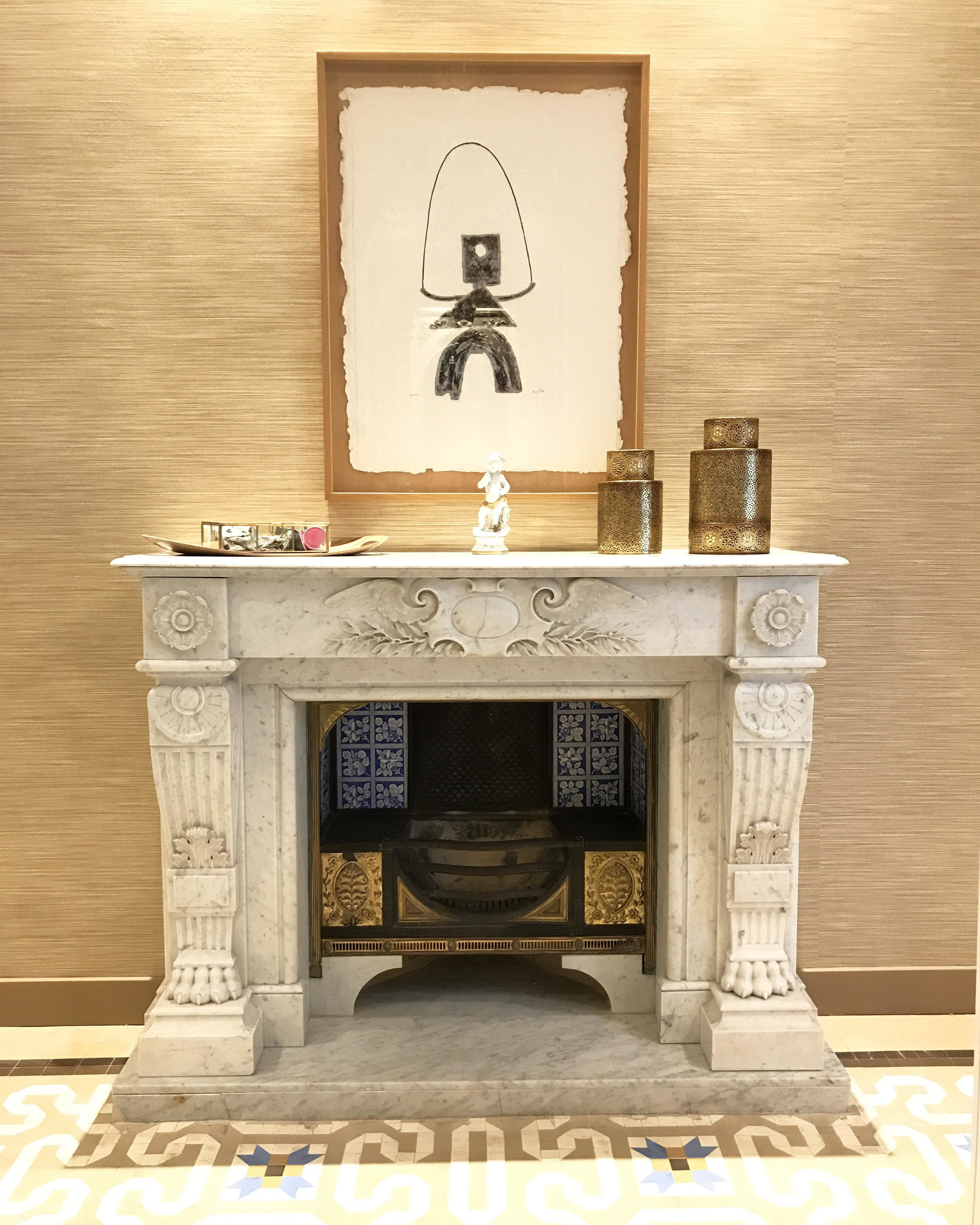 An image of a living room classic luxury marble fireplace with Asian influence accessories and textured silk wall coverings