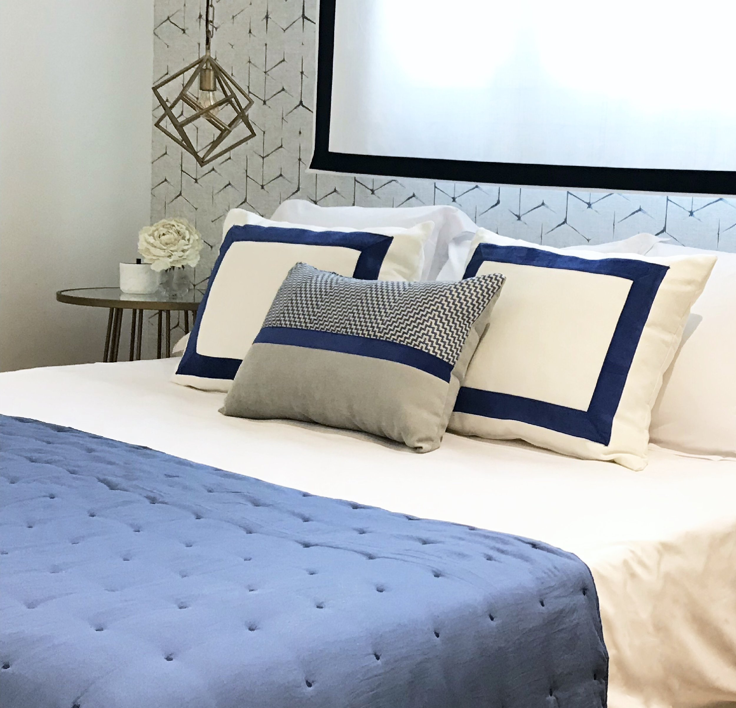 Image of professionally styled bed in blues and off white tones with graphic wallpaper and hanging dynamic light.