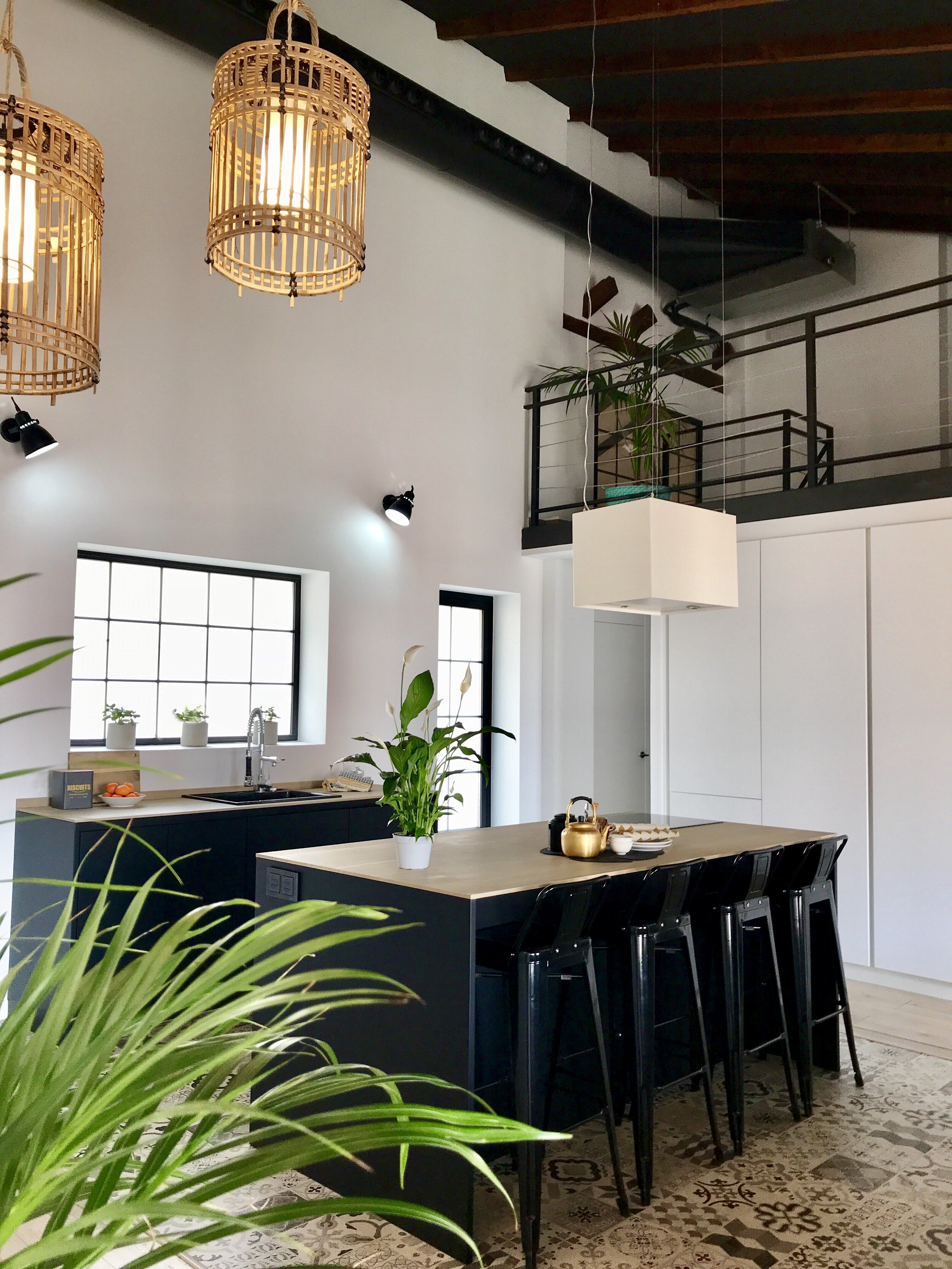 Image of a modern kitchen styled with natural light and hanging lamps and a high beamed ceiling for a warm and strong feeling..