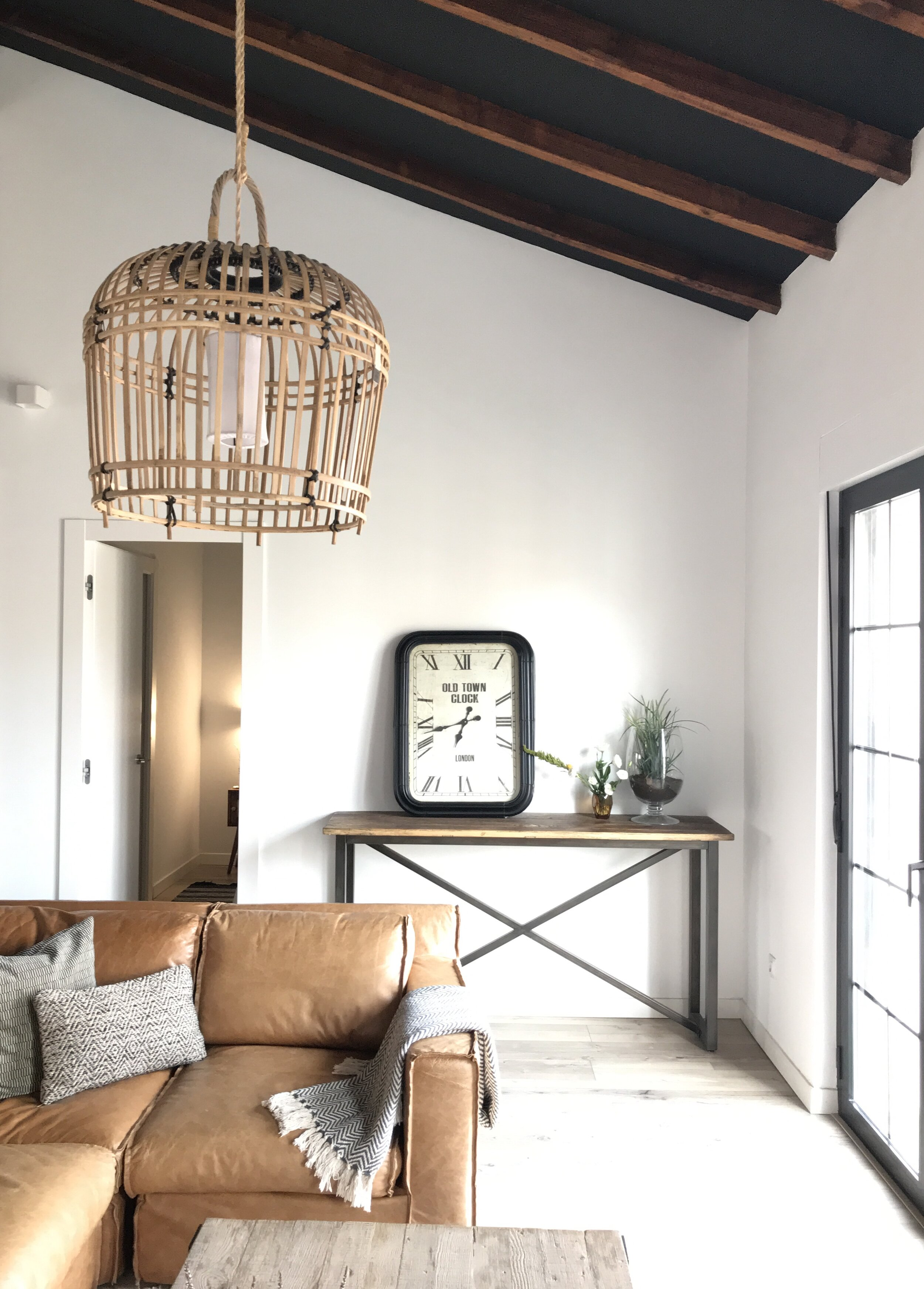 Image of a contemporary living area styled with a warm ochre toned couch, hanging wicker lamp and high beamed ceiling.