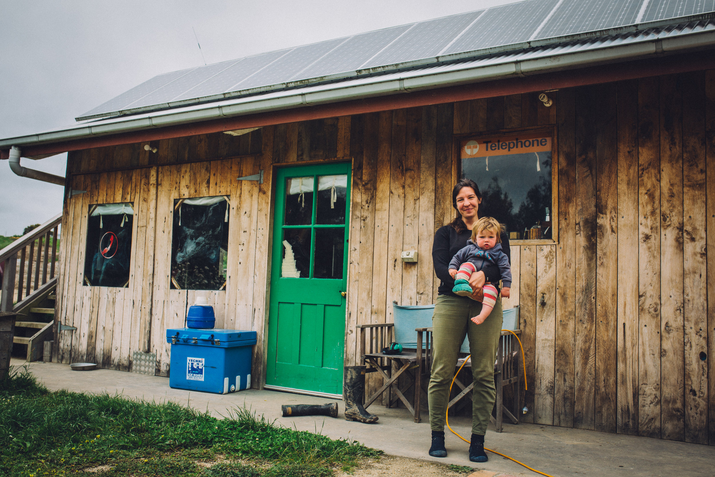 Title:   Amelia Bright and her daughter Hazel in front of their makeshift off-gridhome (new home currently in construction) , Fish Creek, 2016.  Source:  Museums Victoria  Photographer:  Catherine Forge