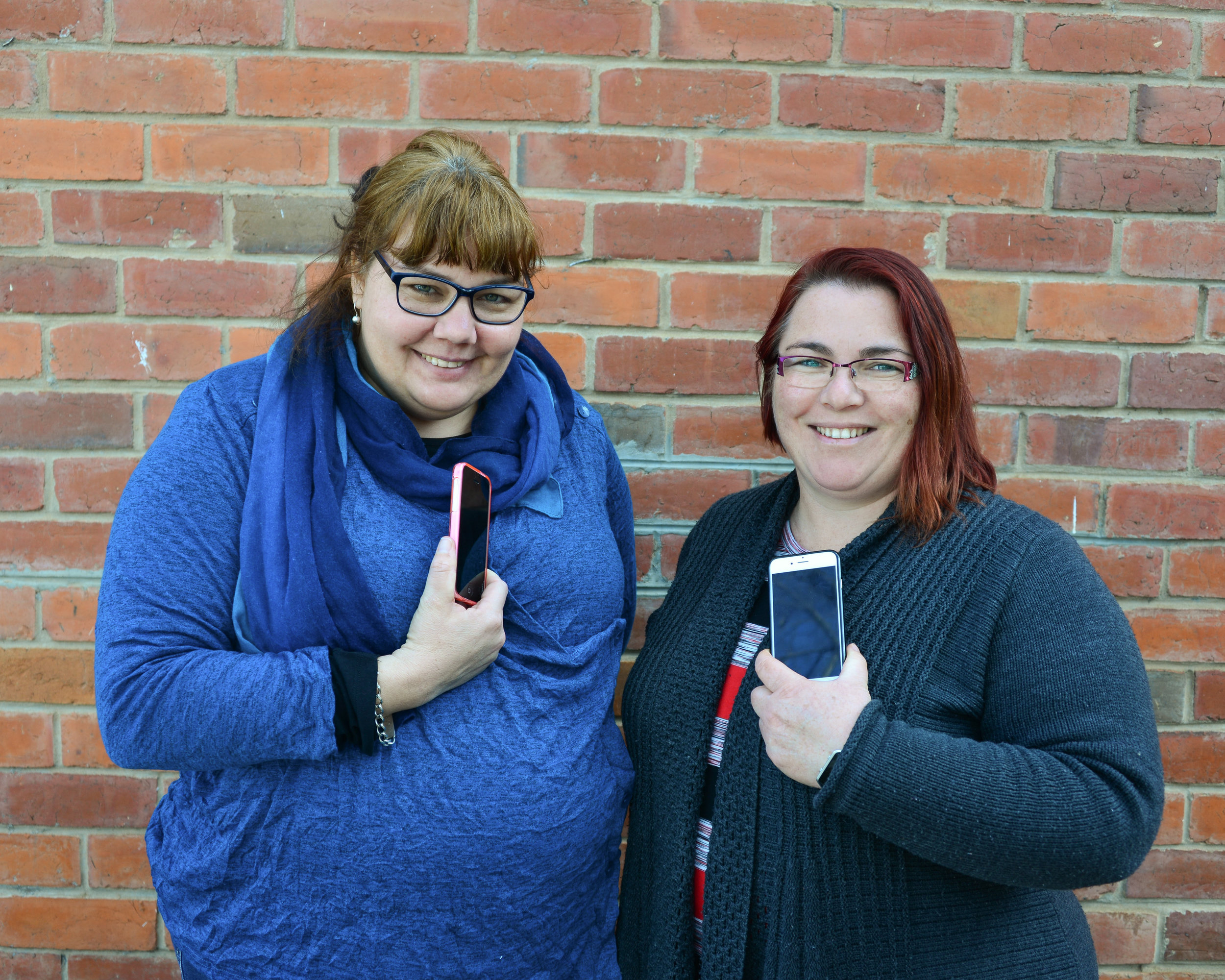 Sarah Parker and Gemma Monk holding their phones, Shepparton, 2016, Source: Museums Victoria, Photographer: Catherine Forge