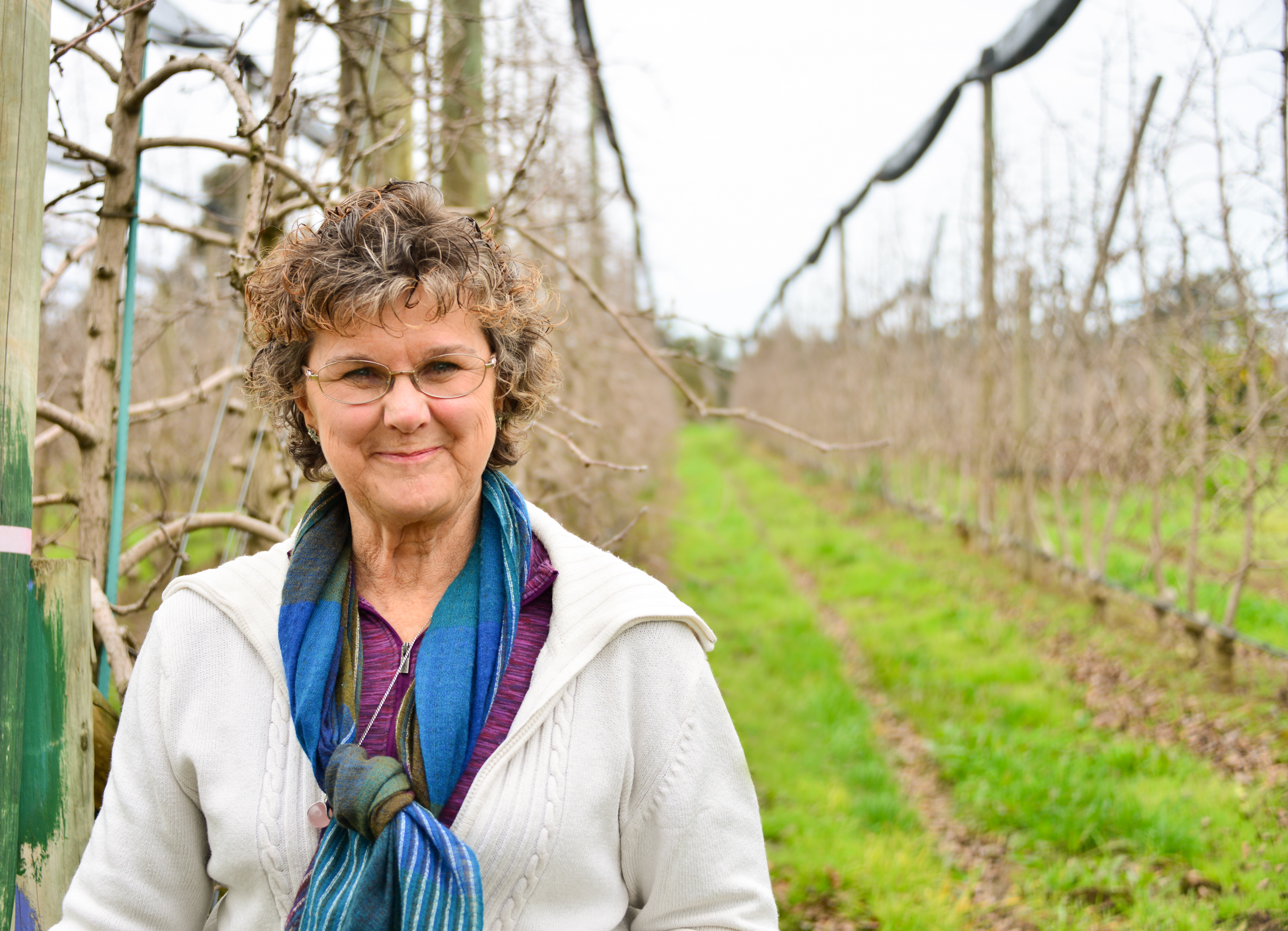 Rien Silverstein standing in front of her orchard in Orvalle, 2016, Source: Museums Victoria, Photographer: Tagen Baker