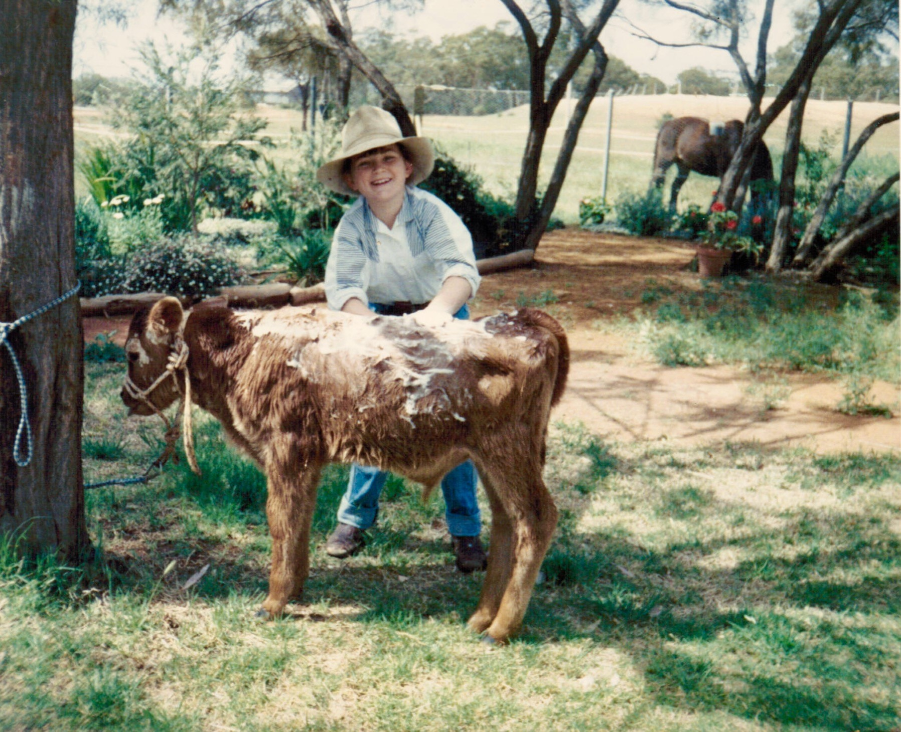 """Lisa washing her poddy calf """"Harry"""", c. 1990, image supplied."""