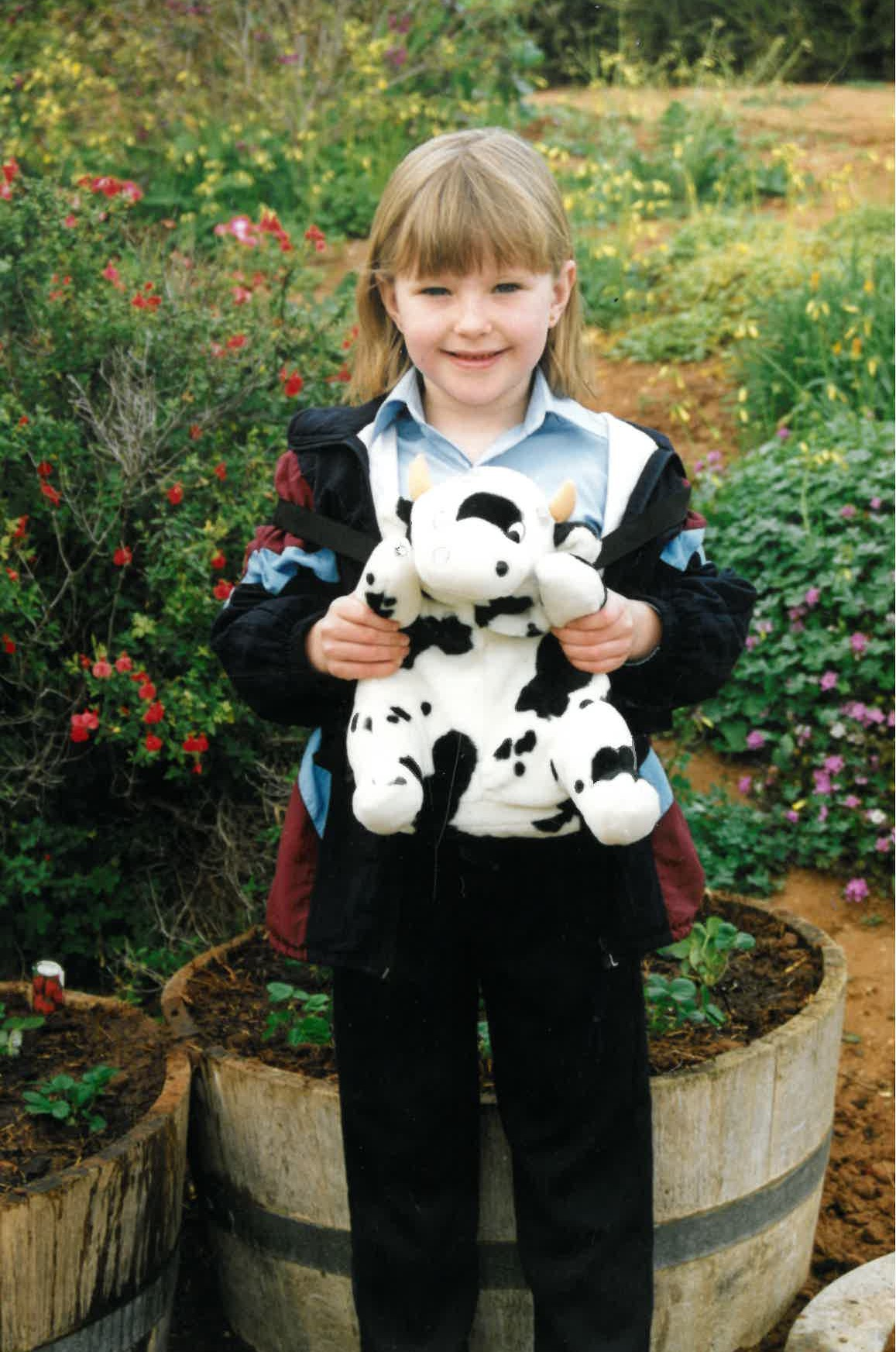 Emily as a child holding her toy cow, image supplied.