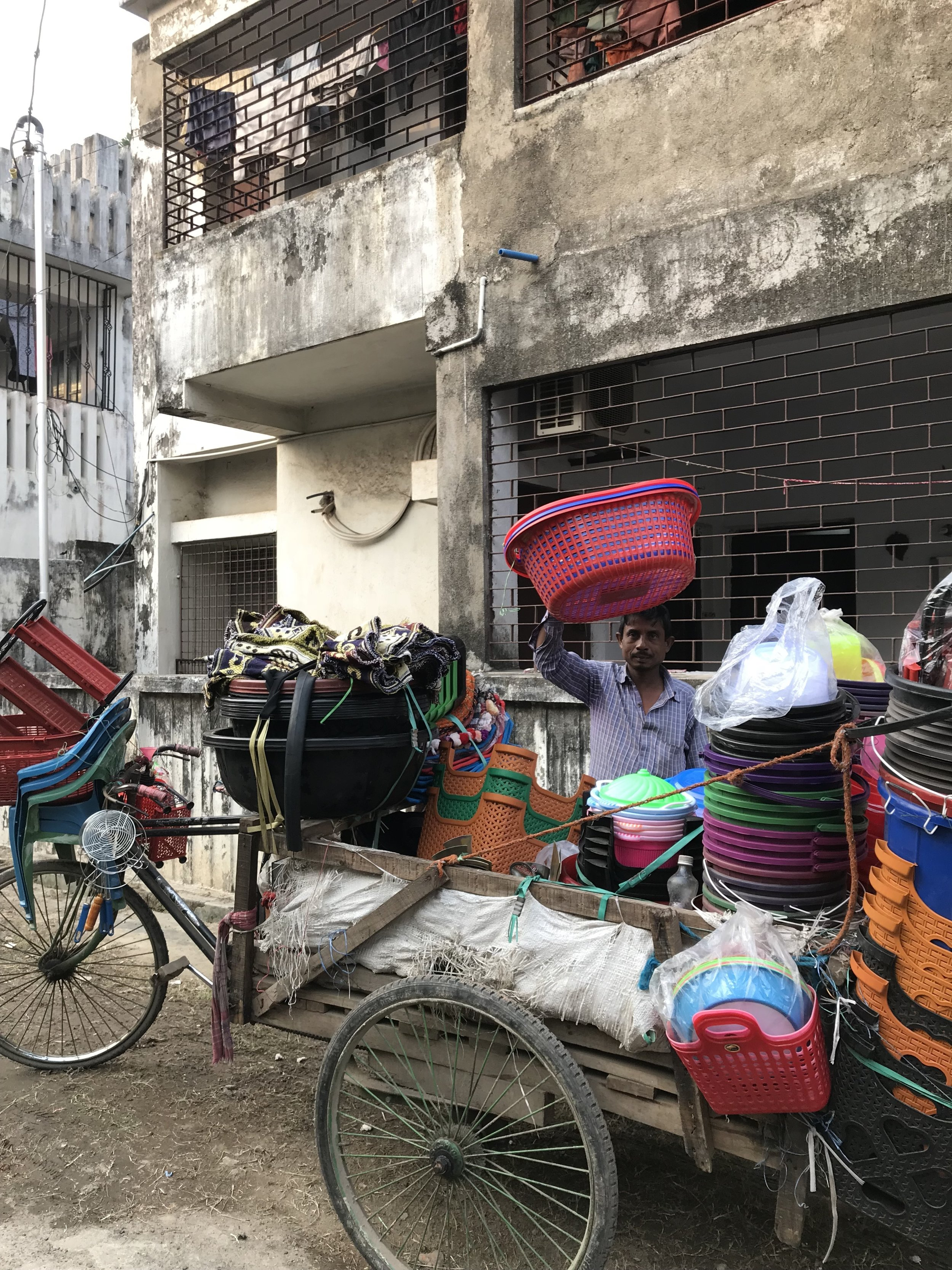 """This photo was taken in front of my grandparents house. The man with all the plastic goods on the bicycle does his rounds selling his product everyday in my grandparents neighbourhood."""